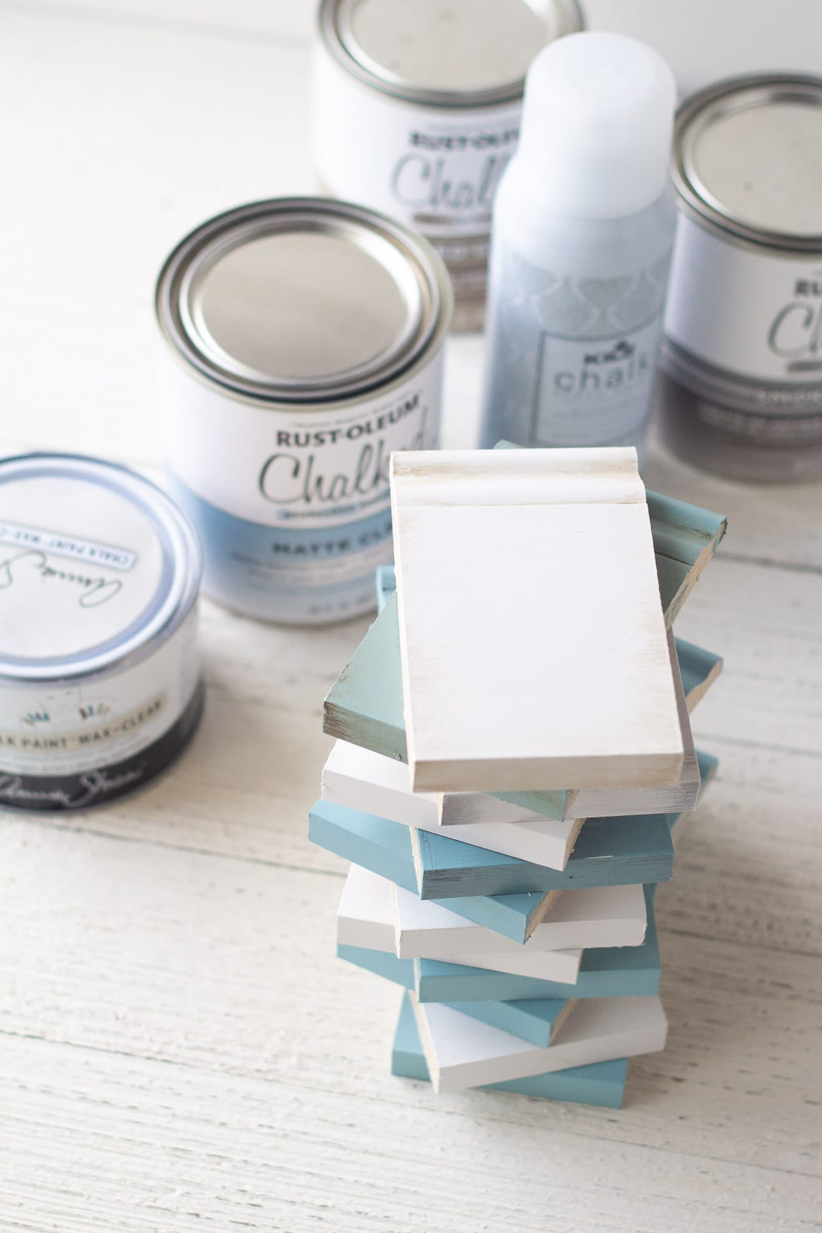 A stack of trim pieces painted with chalk paint and sealed with different top coats.