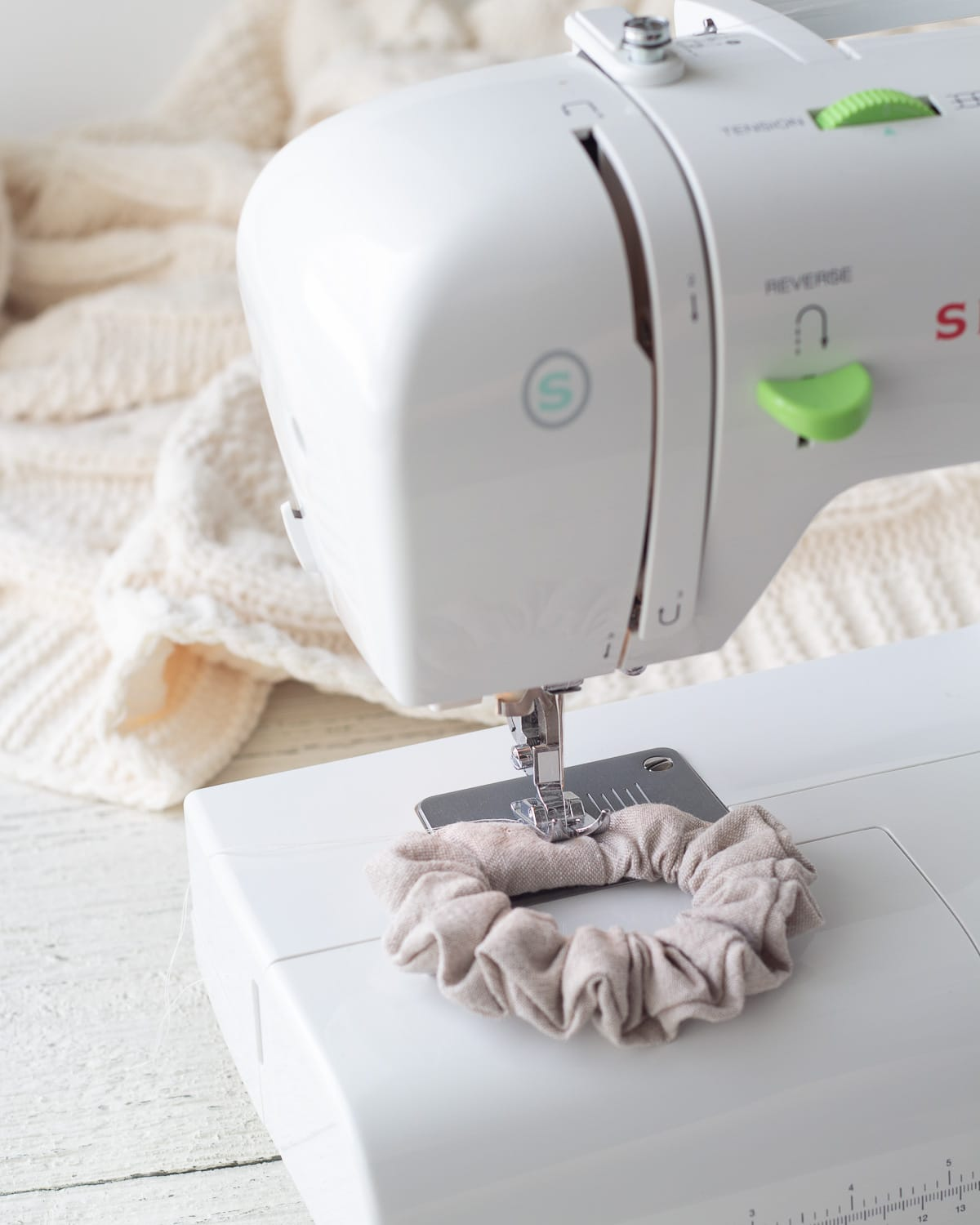 Stitching the final seam on a scrunchie with a sewing machine.