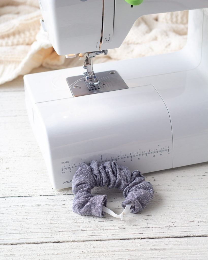 Stitching the elastic closed on a handmade scrunchie made with blue linen.
