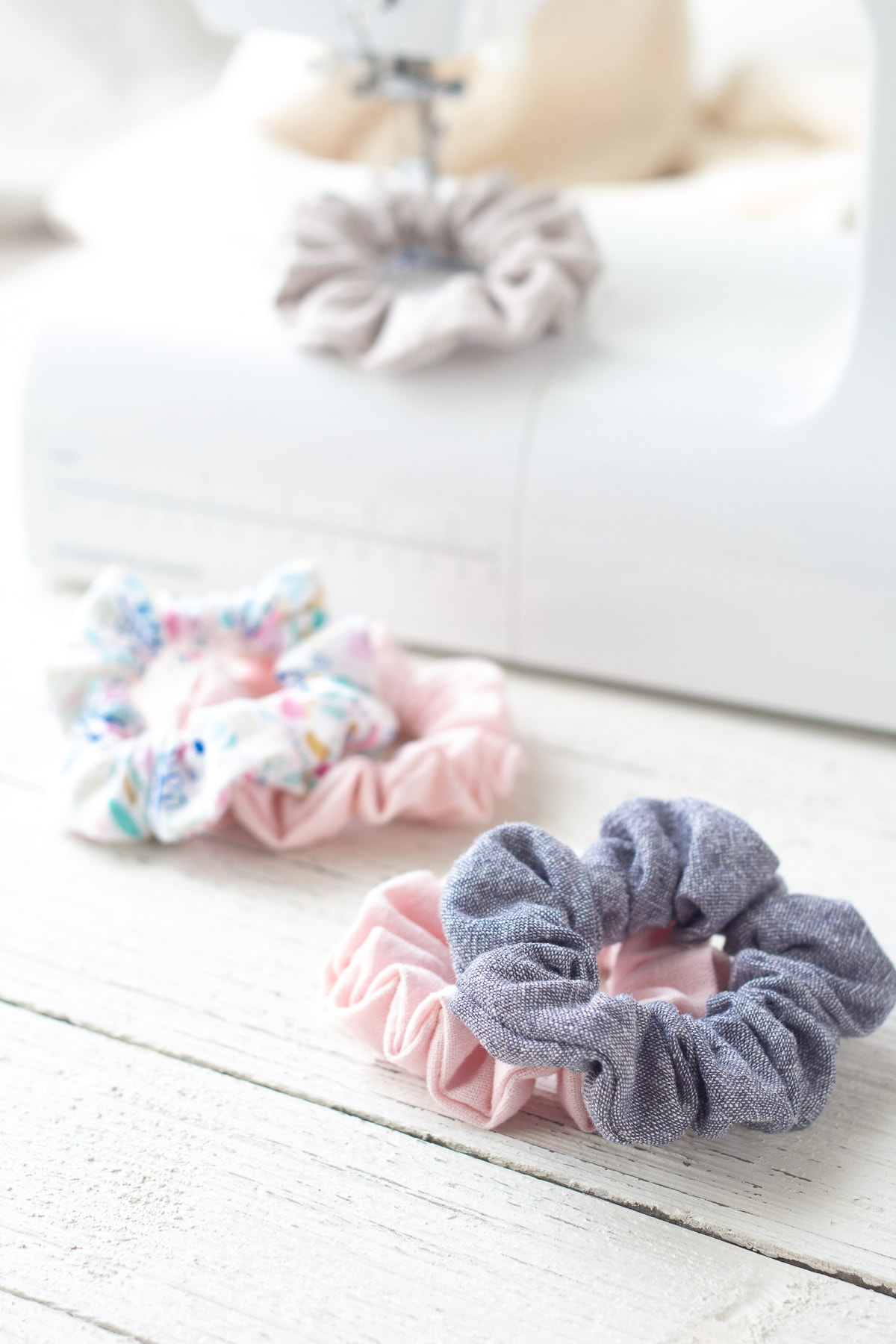 Handmade linen scrunchies around a white sewing machine.