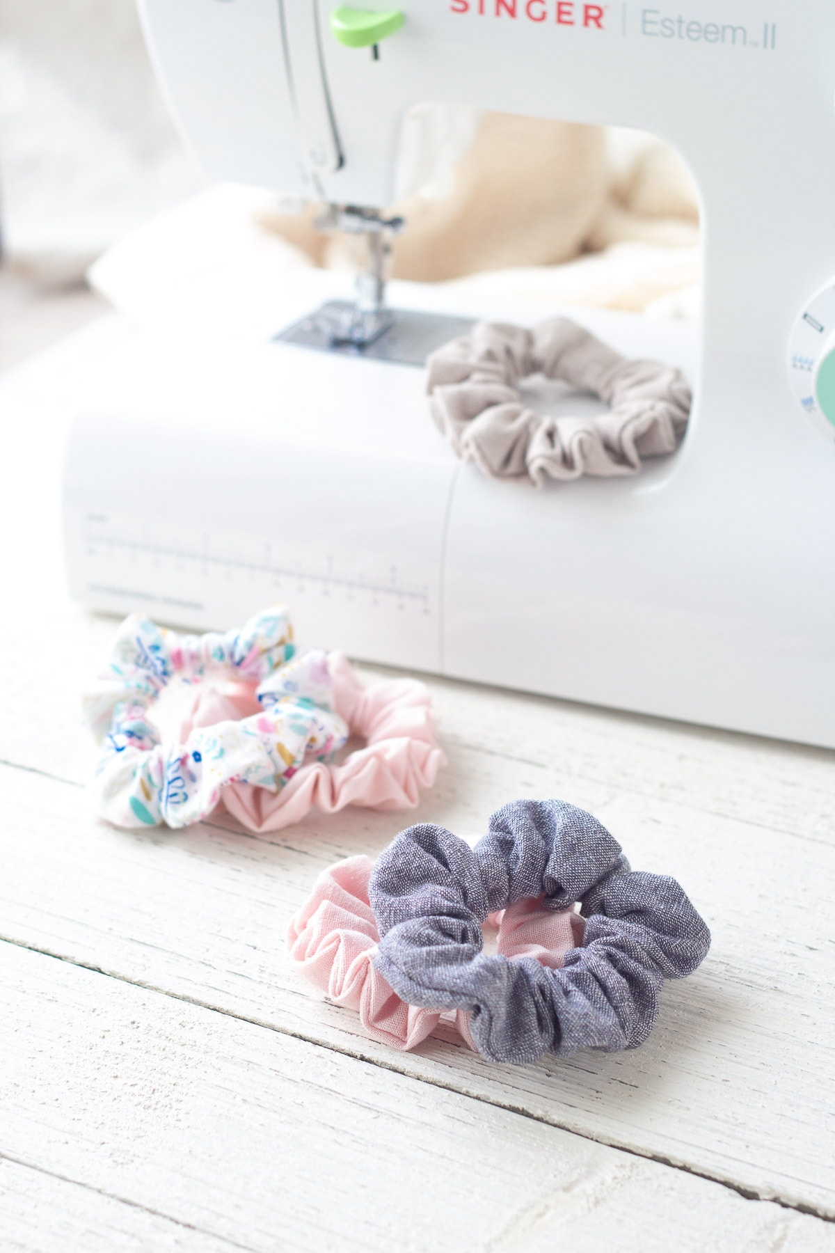 """Scrunchies arranged around a sewing machine made with tutorial, """"how to sew scrunchies with neat seams""""."""