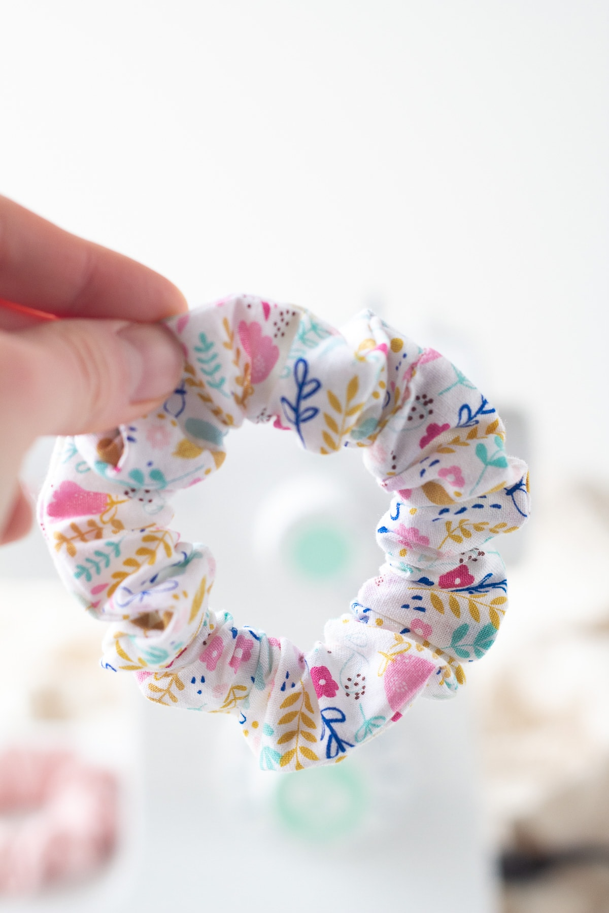 Holding a handmade colorful floral scrunchie.