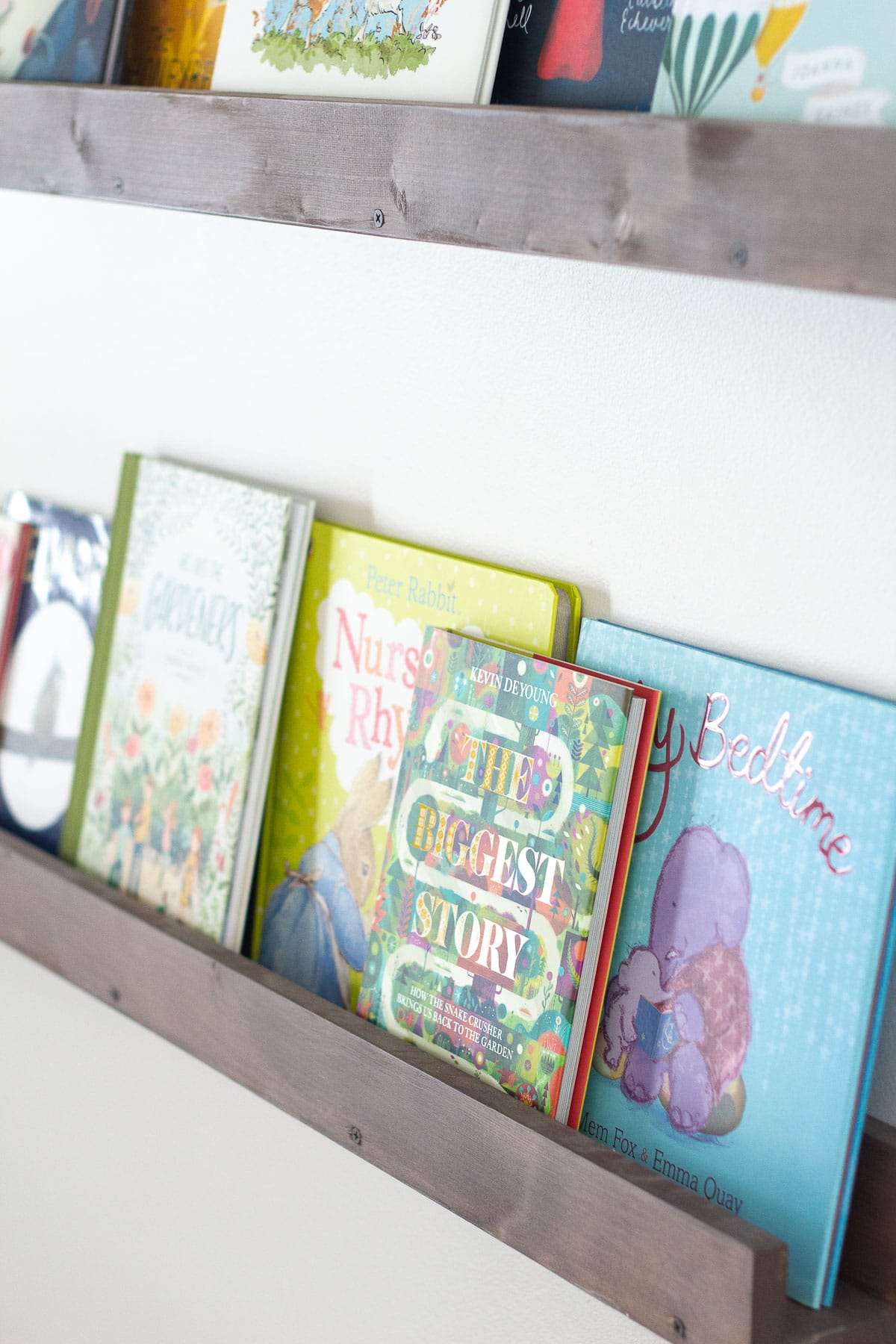 The Biggest Story and other children's books displayed on floating wall shelves.