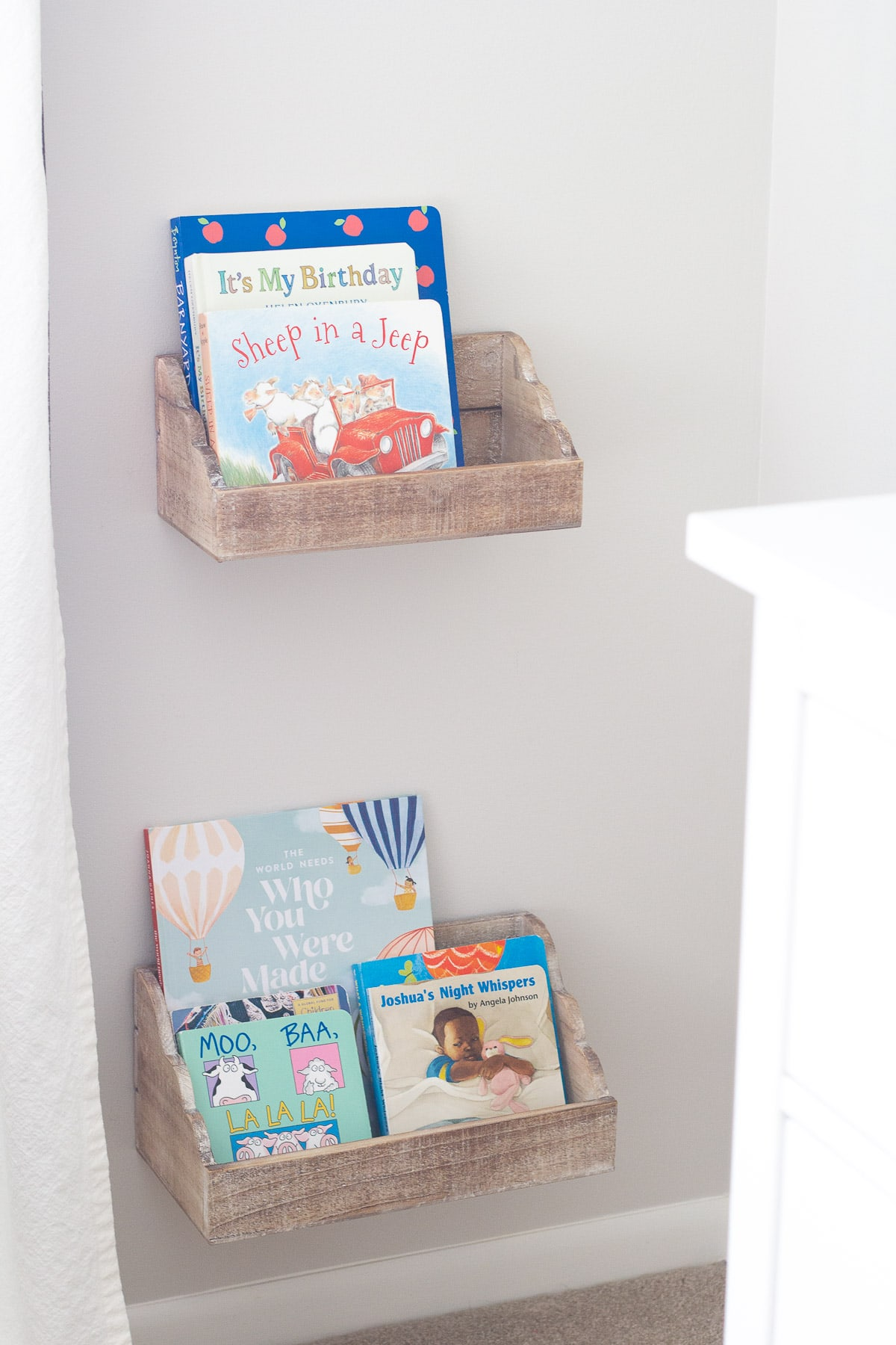 Kids' books in a nursery displayed in floating shelves.