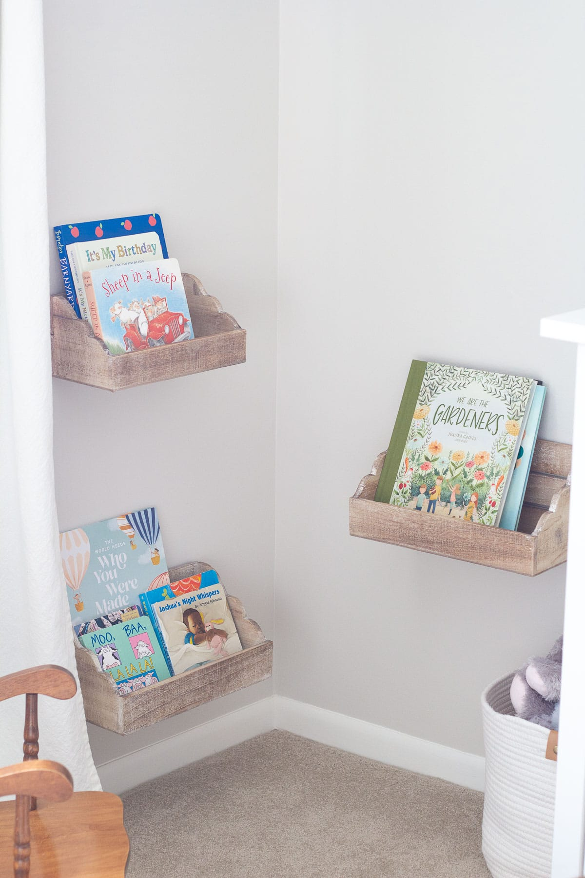 Kids' books in a nursery displayed in floating shelves from Hobby Lobby.