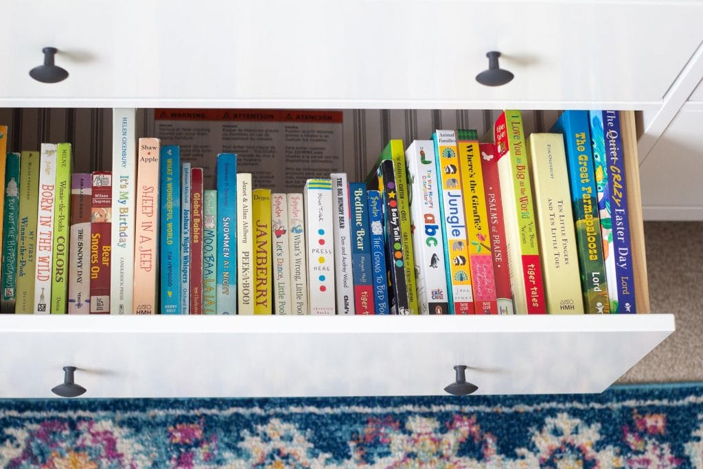 A display of baby board books stored in a drawer.