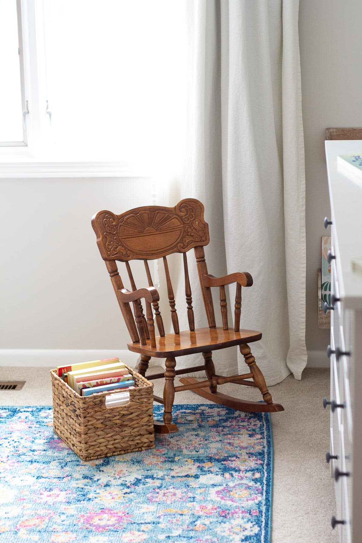 Baby board books stored in a basket alongside a vintage toddler's rocking chair.