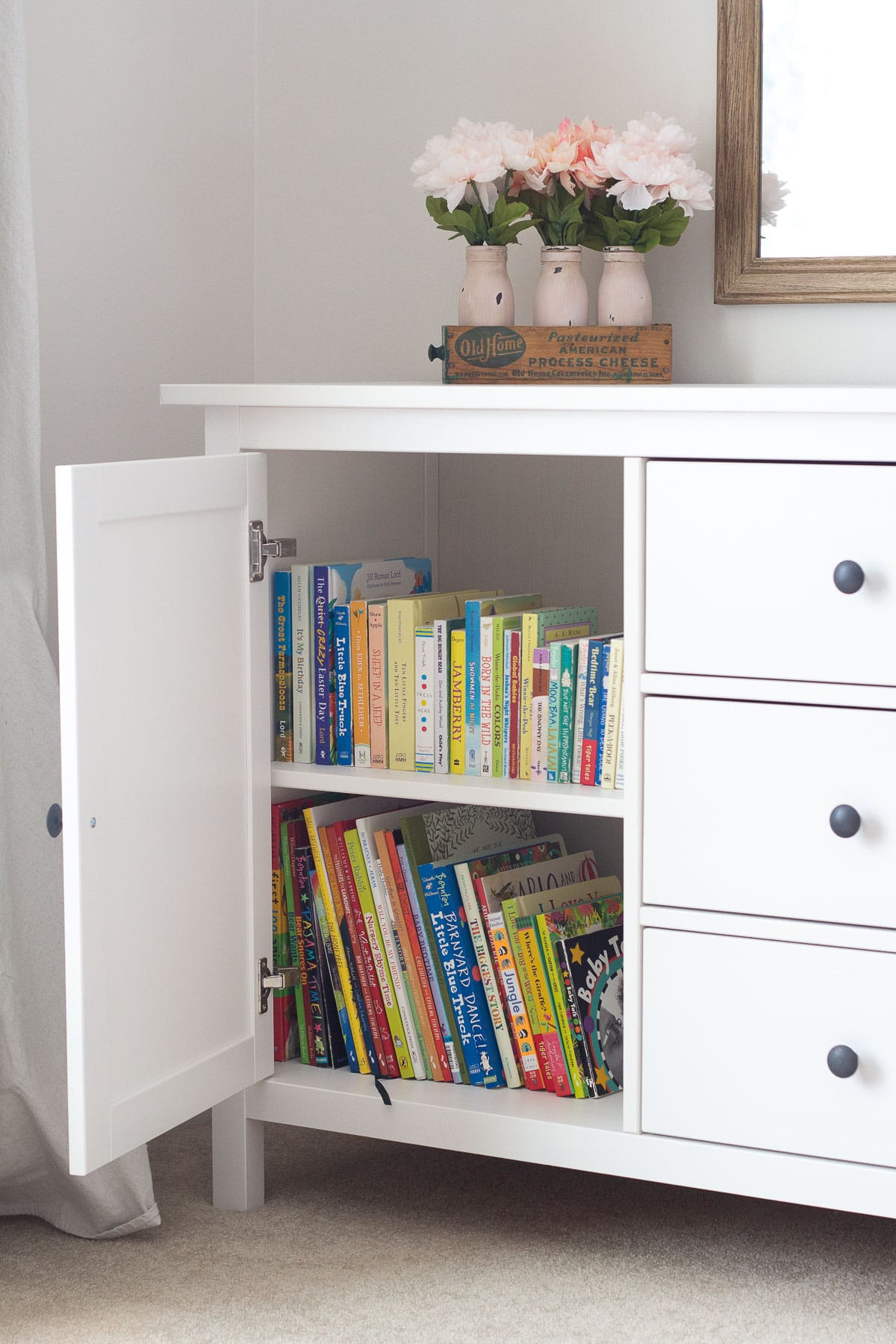 An open cupboard displaying children's picture books and board books.