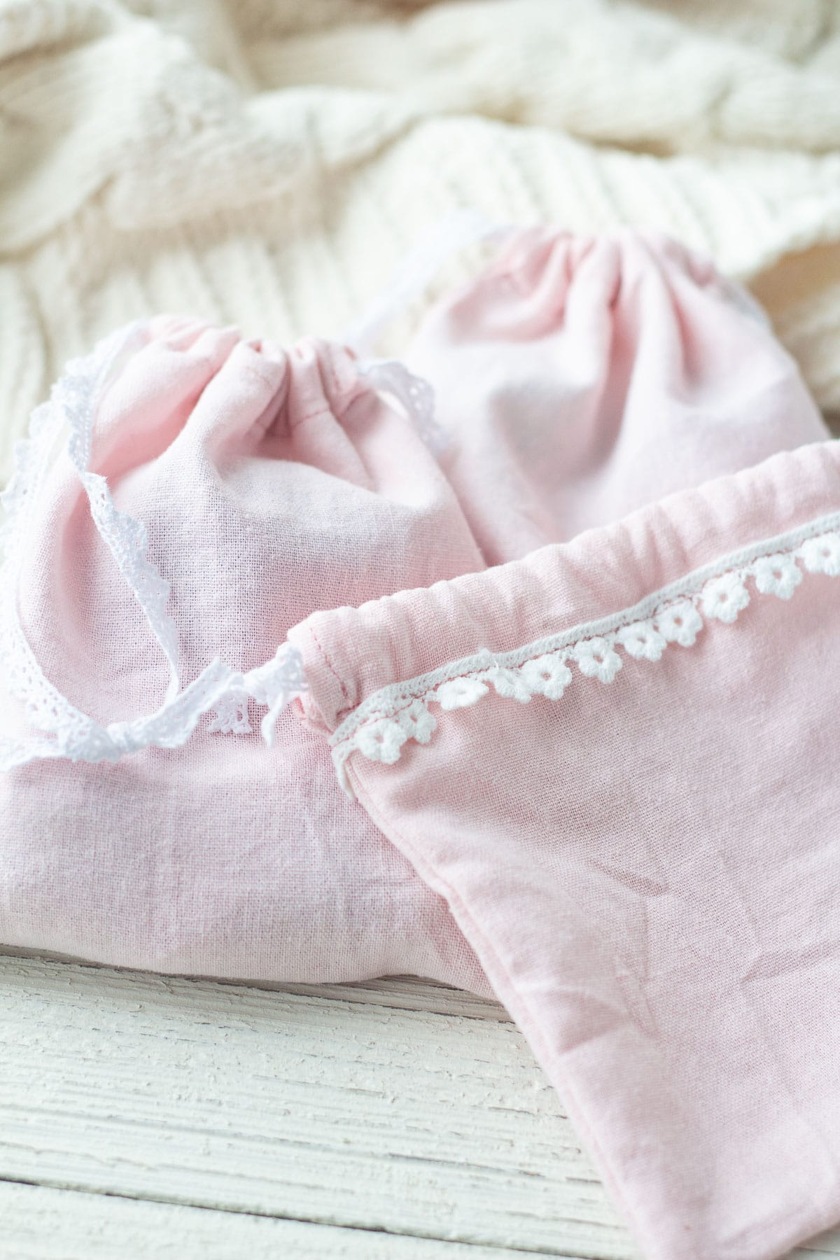 Pink linen drawstring bags with a lace edge.