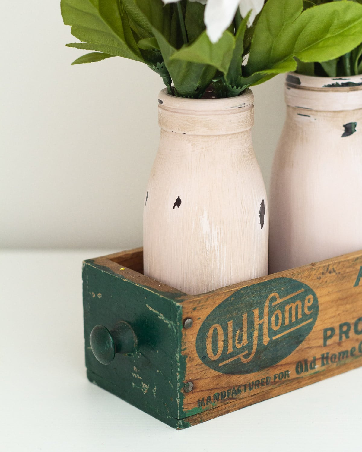 Chalk painted and distressed milk bottles in a vintage cheese box.