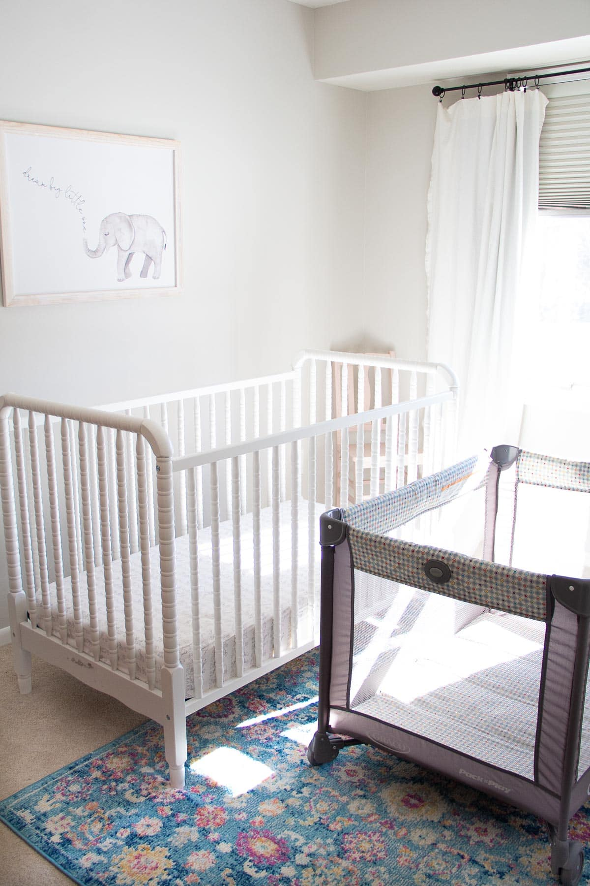 A white Jenny Lind Crib alongside a gray Graco pack and play.
