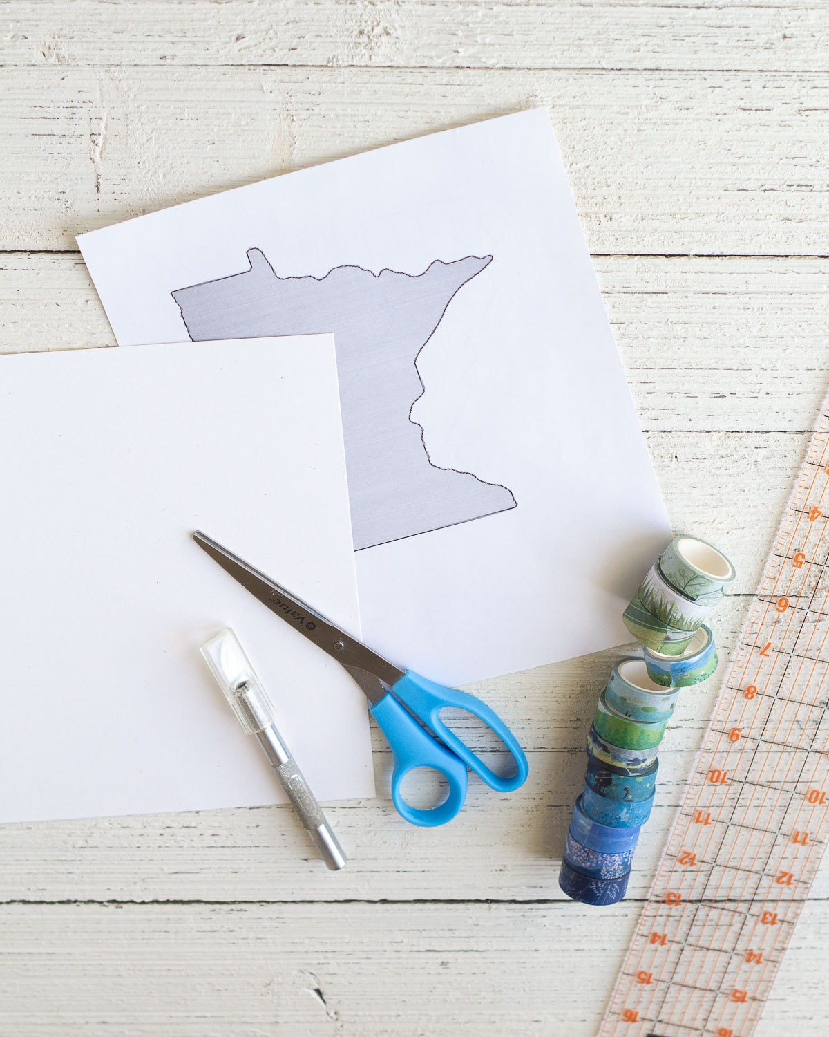 A ruler, washi tape, scissors, craft knife, cardstock, and a template of the state of Minnesota.