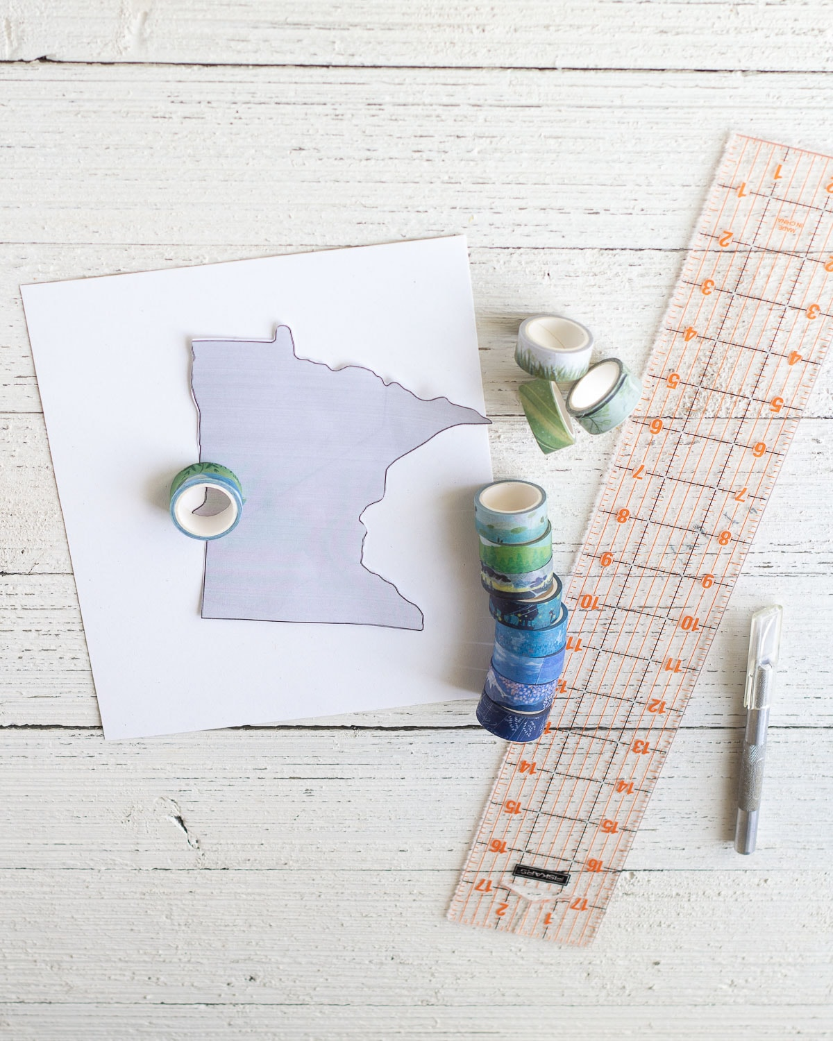 A ruler, washi tape, craft knife, cardstock, and a template of the state of Minnesota.