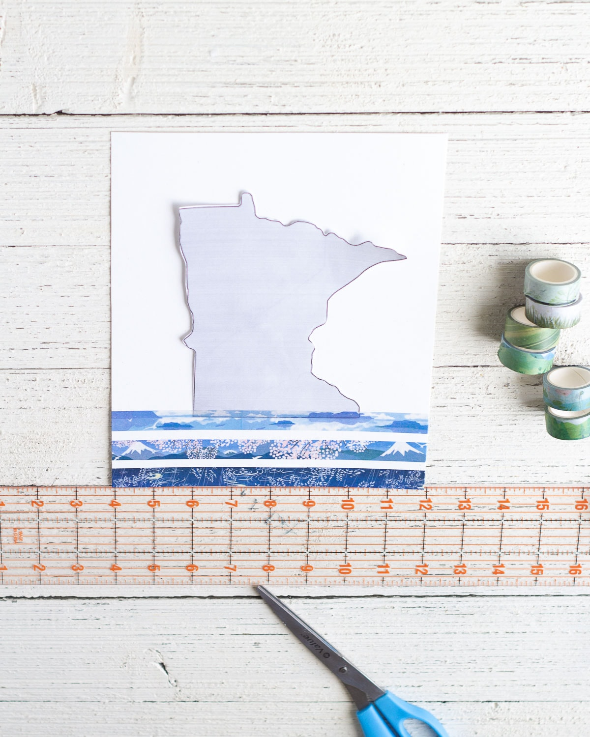 Measuring washi tape stripes onto a piece of cardstock for a home state wall art design.