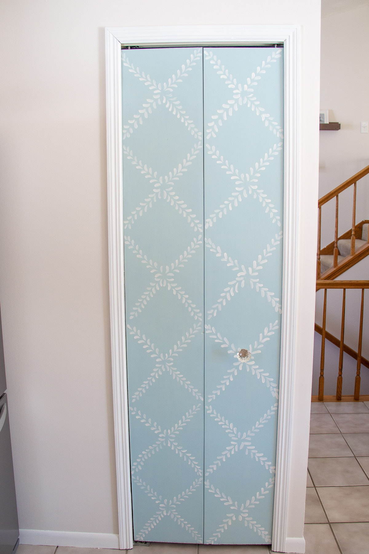 A bi-fold pantry door painted with light blue chalk paint and a floral design.