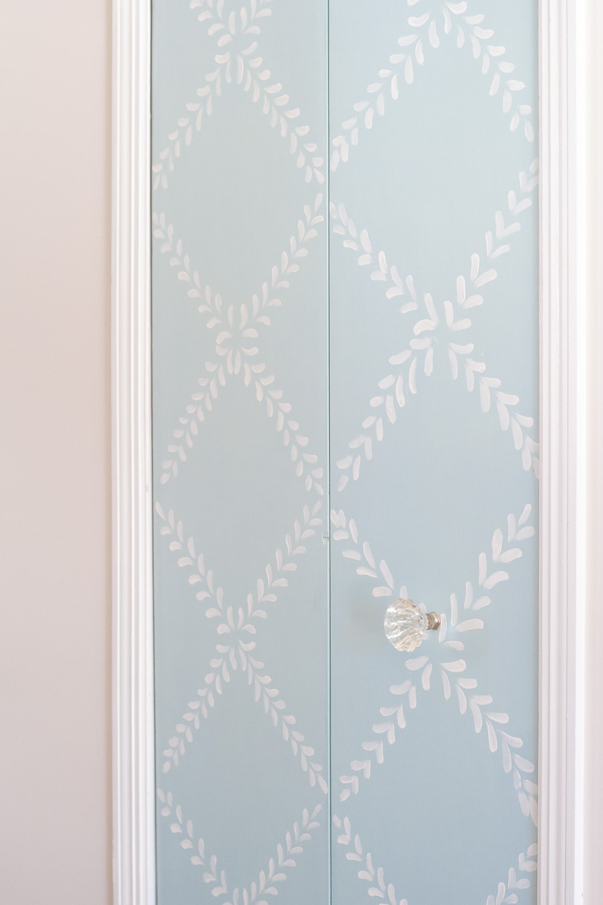 An old bi-fold pantry door updated with chalk paint in a floral design.