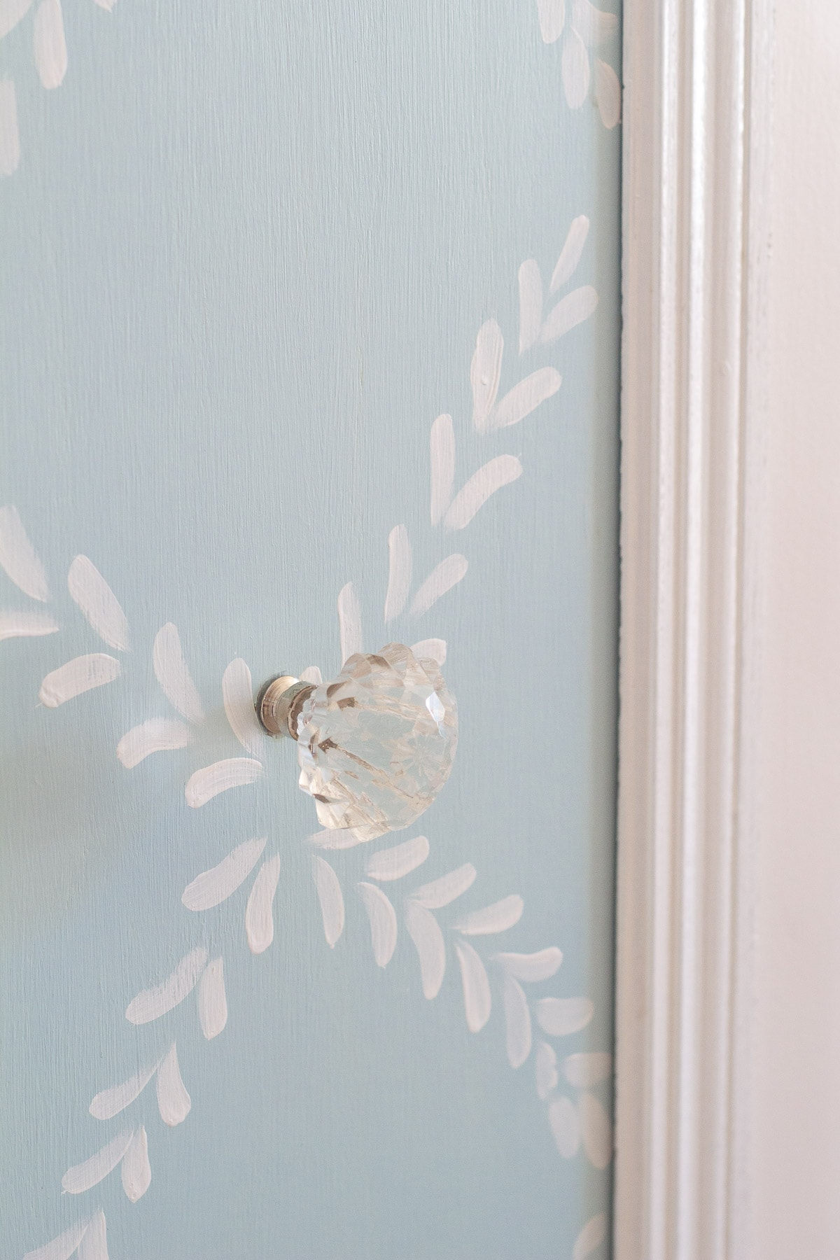 A glass doorknob installed on a chalk-painted pantry door.
