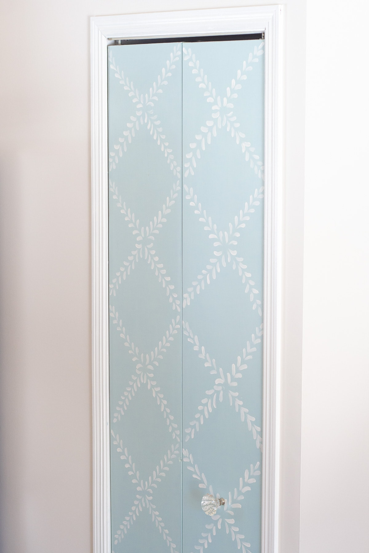 A pantry door painted with blue chalk paint and a white floral design.