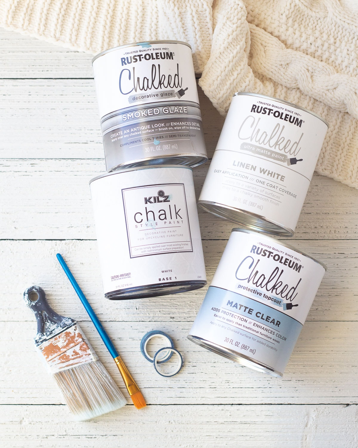 Chalk paint cans, paintbrushes, and washi tape on a wooden surface.