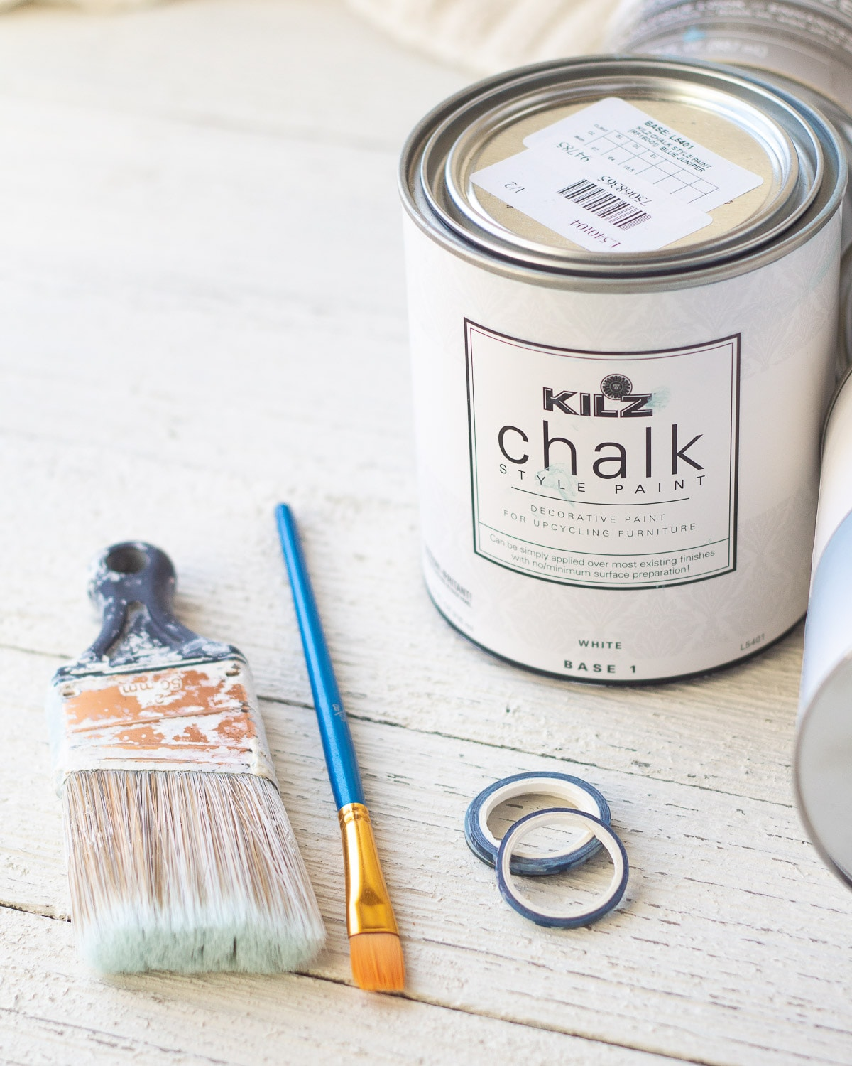 Paint brushes, washi tape, and a can of chalk style paint.