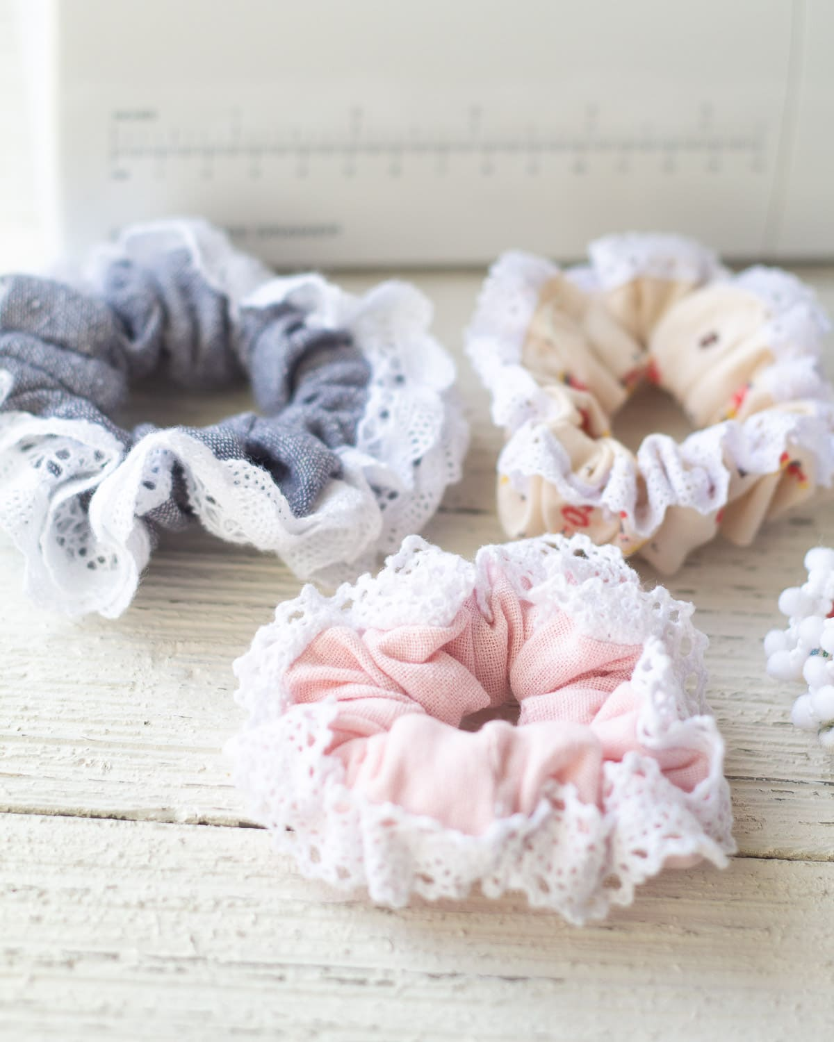 Three lace-trimmed scrunchies on a wooden surface.