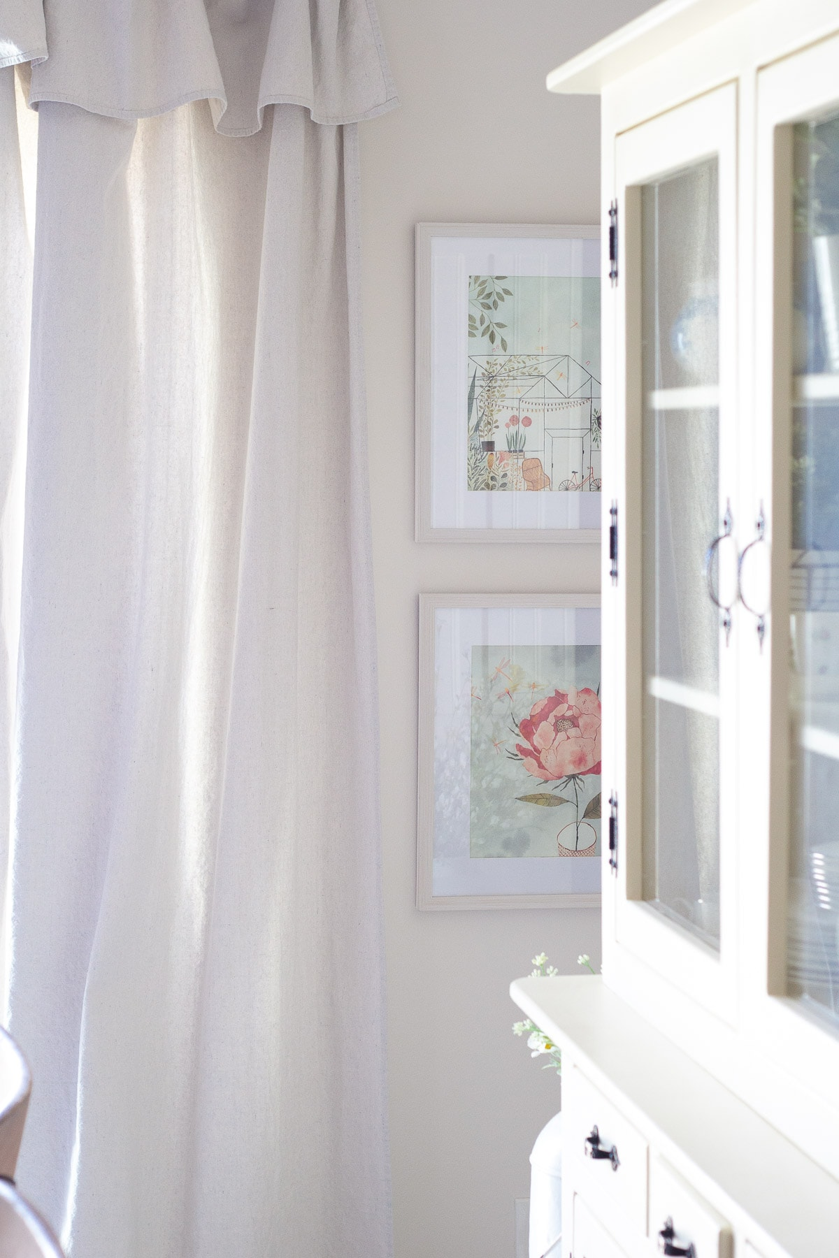Two framed pictures on a white wall surrounded by drop cloth curtains and a white hutch.