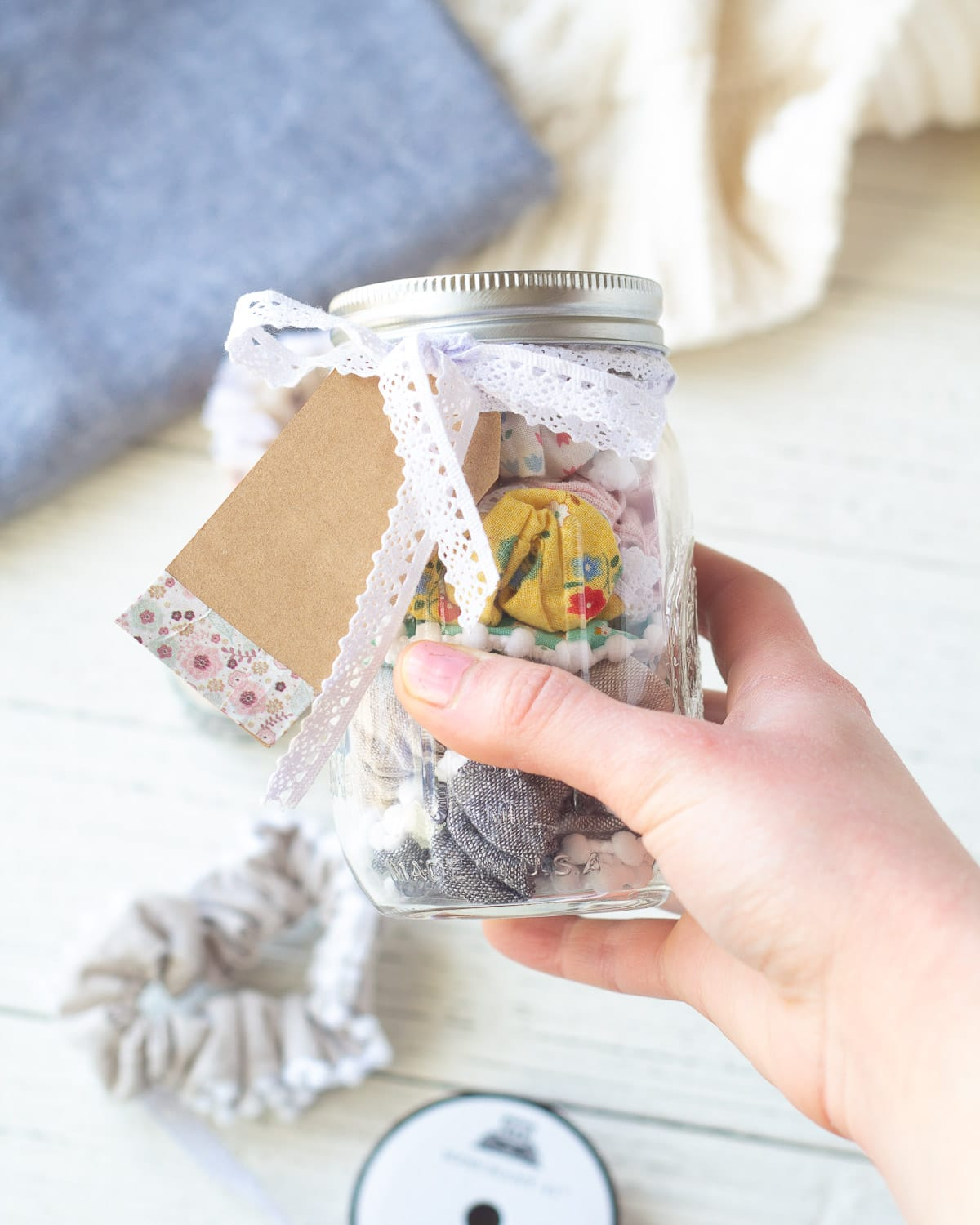 Holding a mason jar filled with scrunchies.