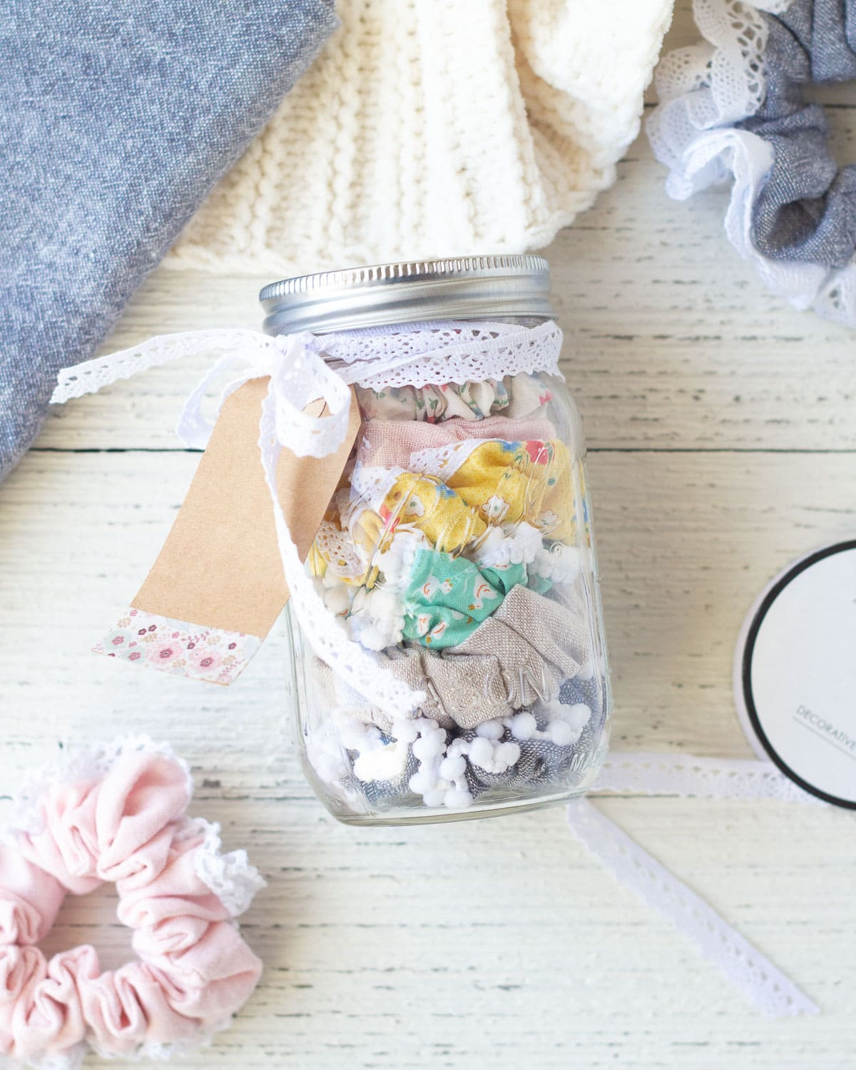 A mason jar filled with scrunchies on a wooden background.