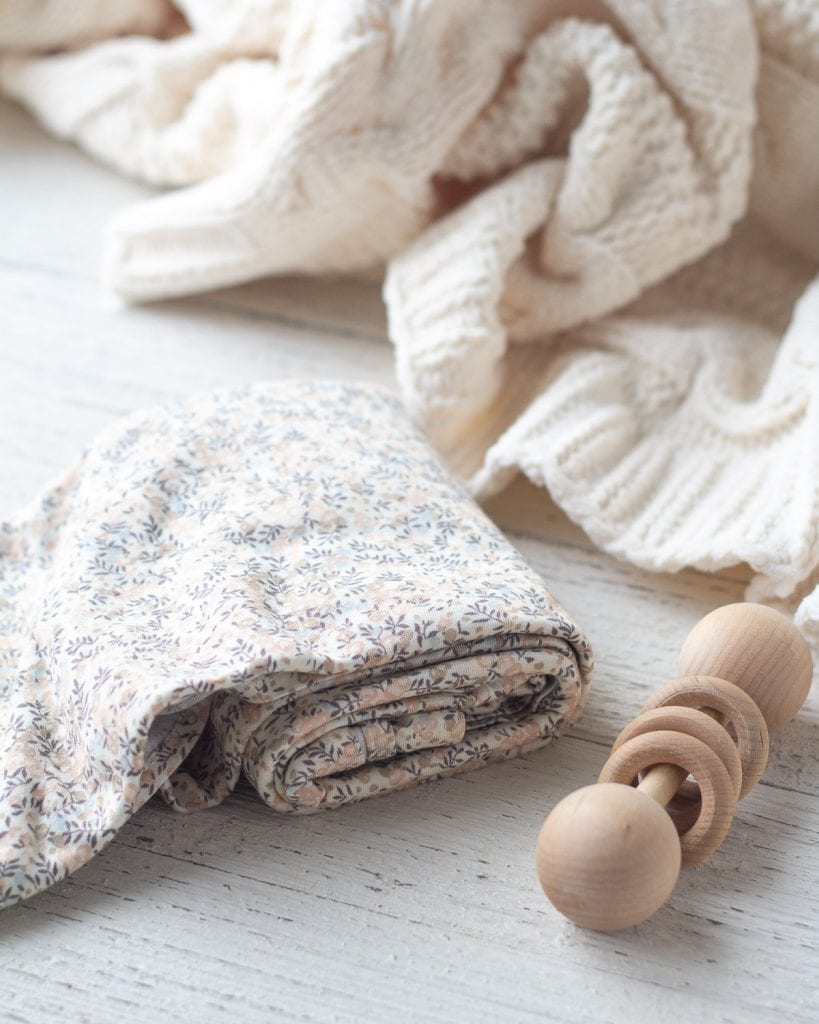 A floral baby swaddle and a wooden rattle.