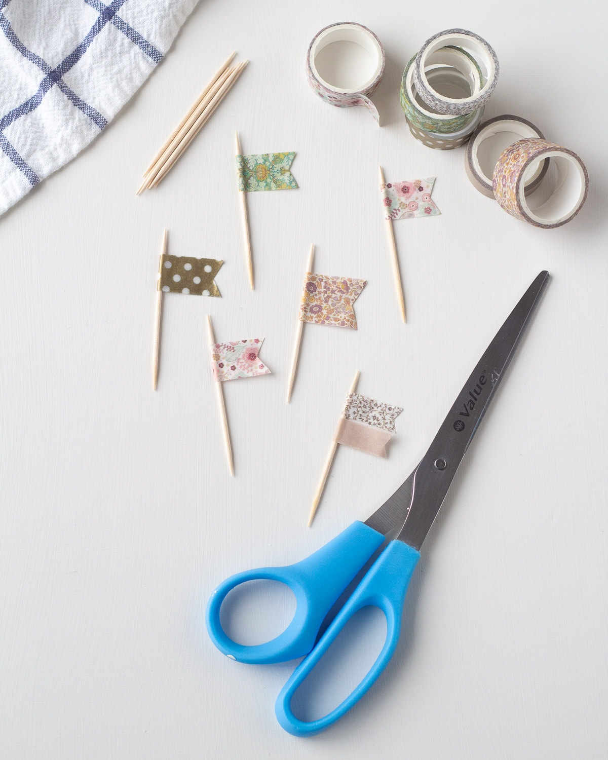 Washi tape flags, spools of washi tape, and scissors on white background.