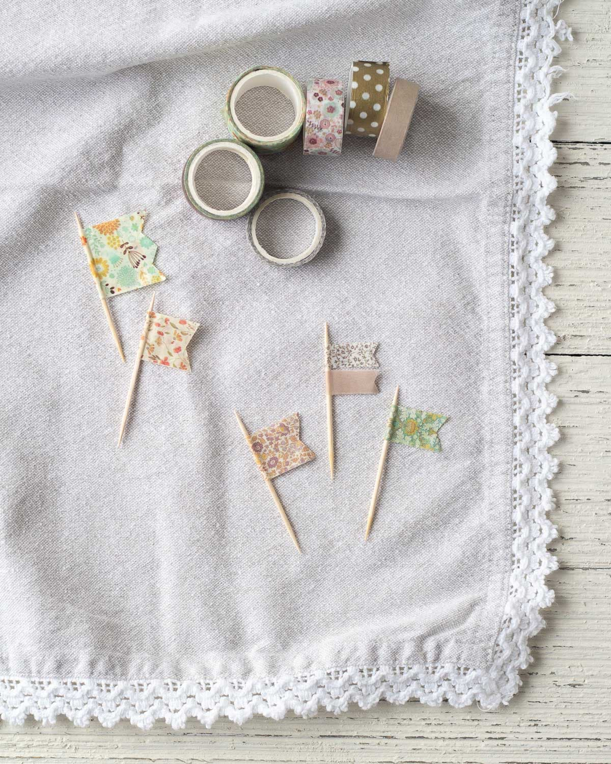 Washi tape flags arranged on linen fabric.