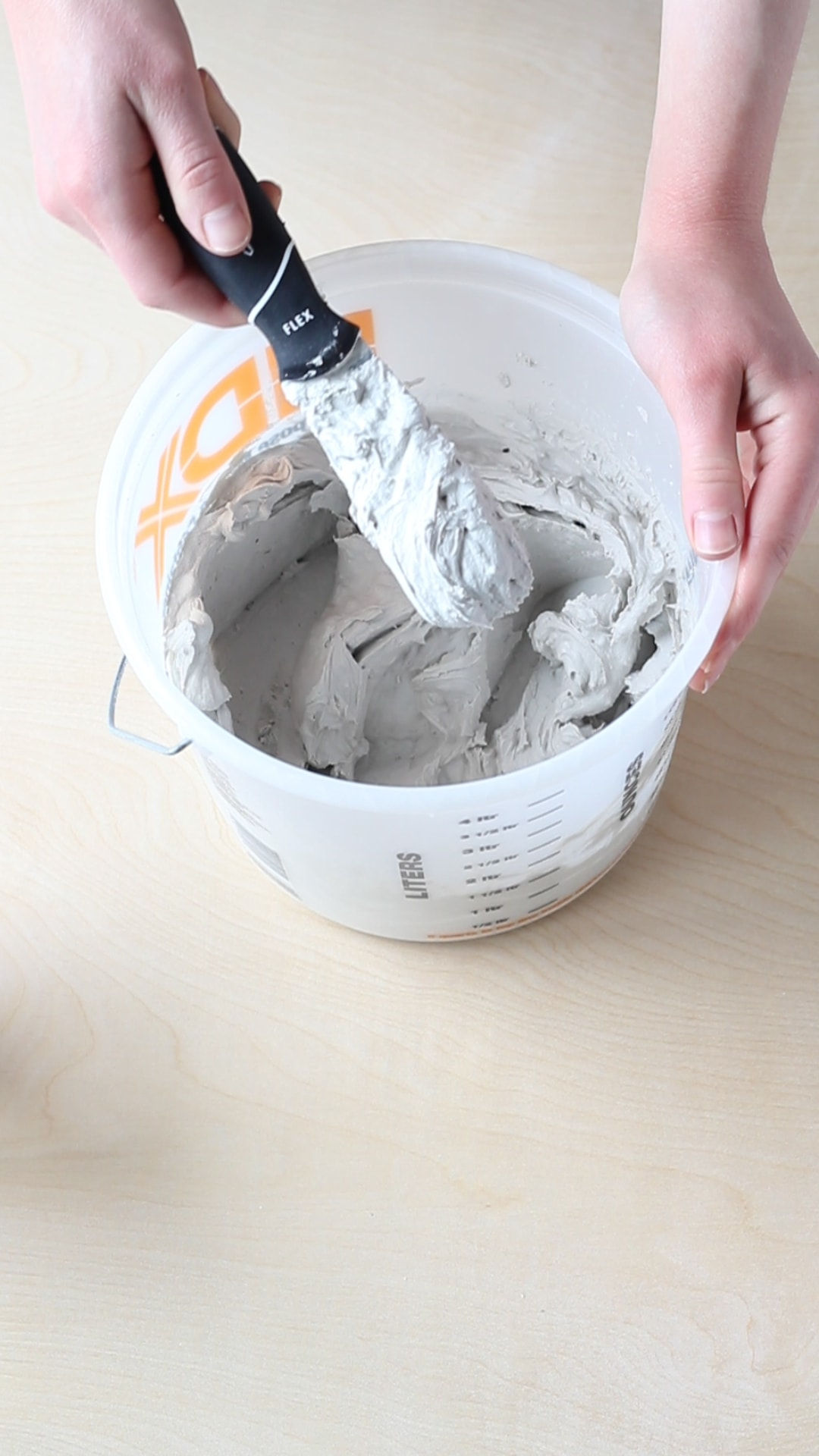 A bucket of mixed joint compound and a putty knife.