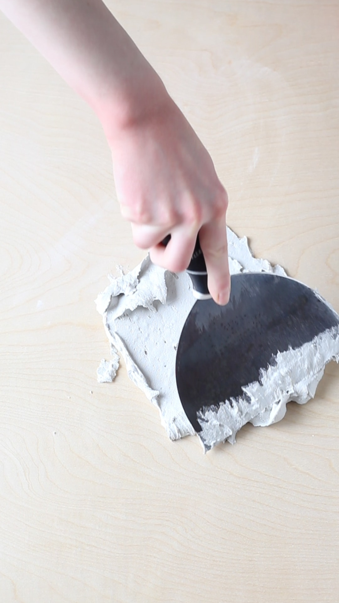 Spreading joint compound onto a plywood sheet to make a diy textured photography background.