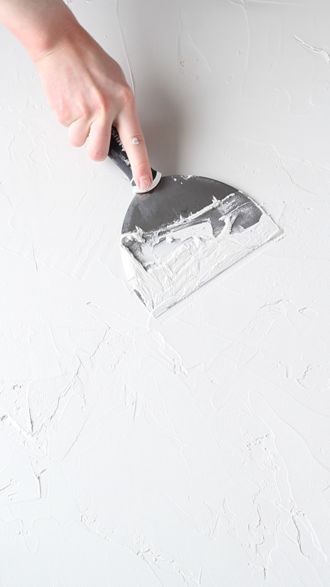 Applying joint compound to a board to make a diy photography backdrop.