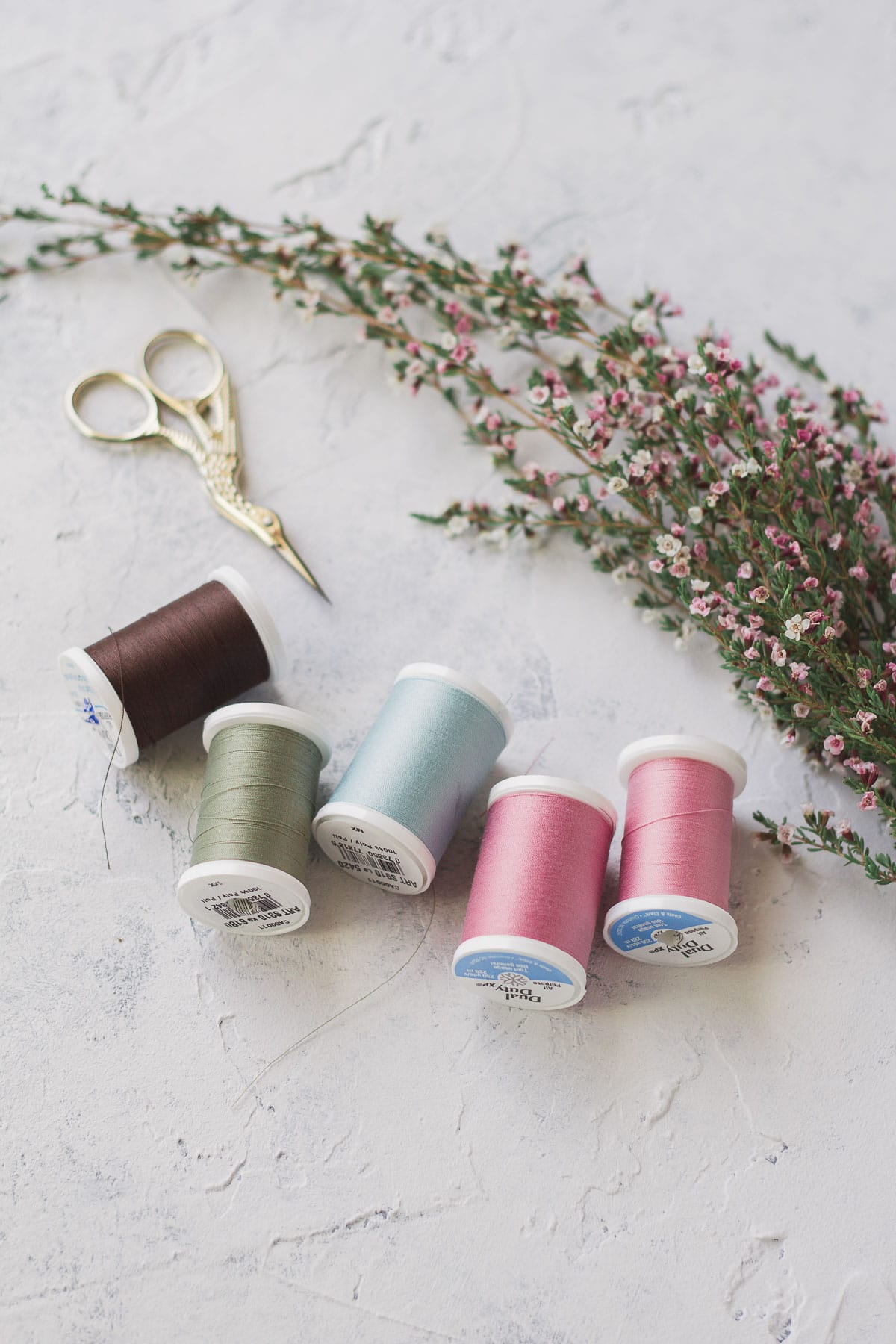 Sewing thread, embroidery scissors, and a spray of pink flowers on a textured background.