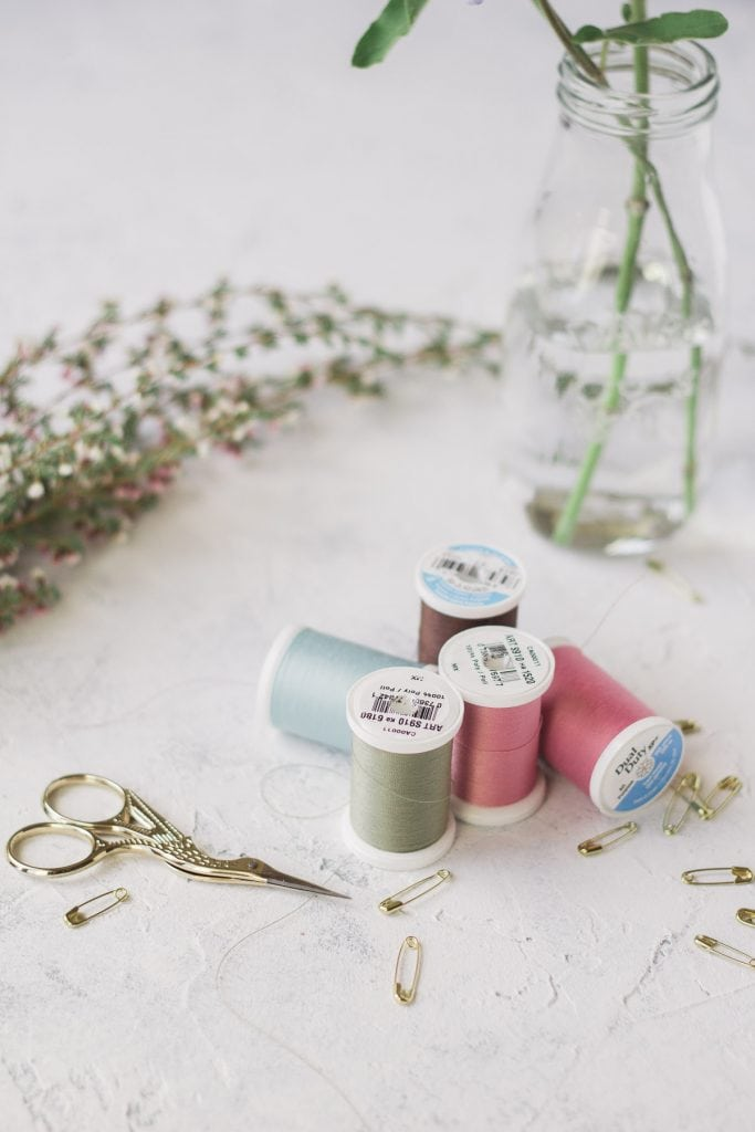 Colorful sewing thread, gold safety pins, and gold embroidery scissors on a textured background.
