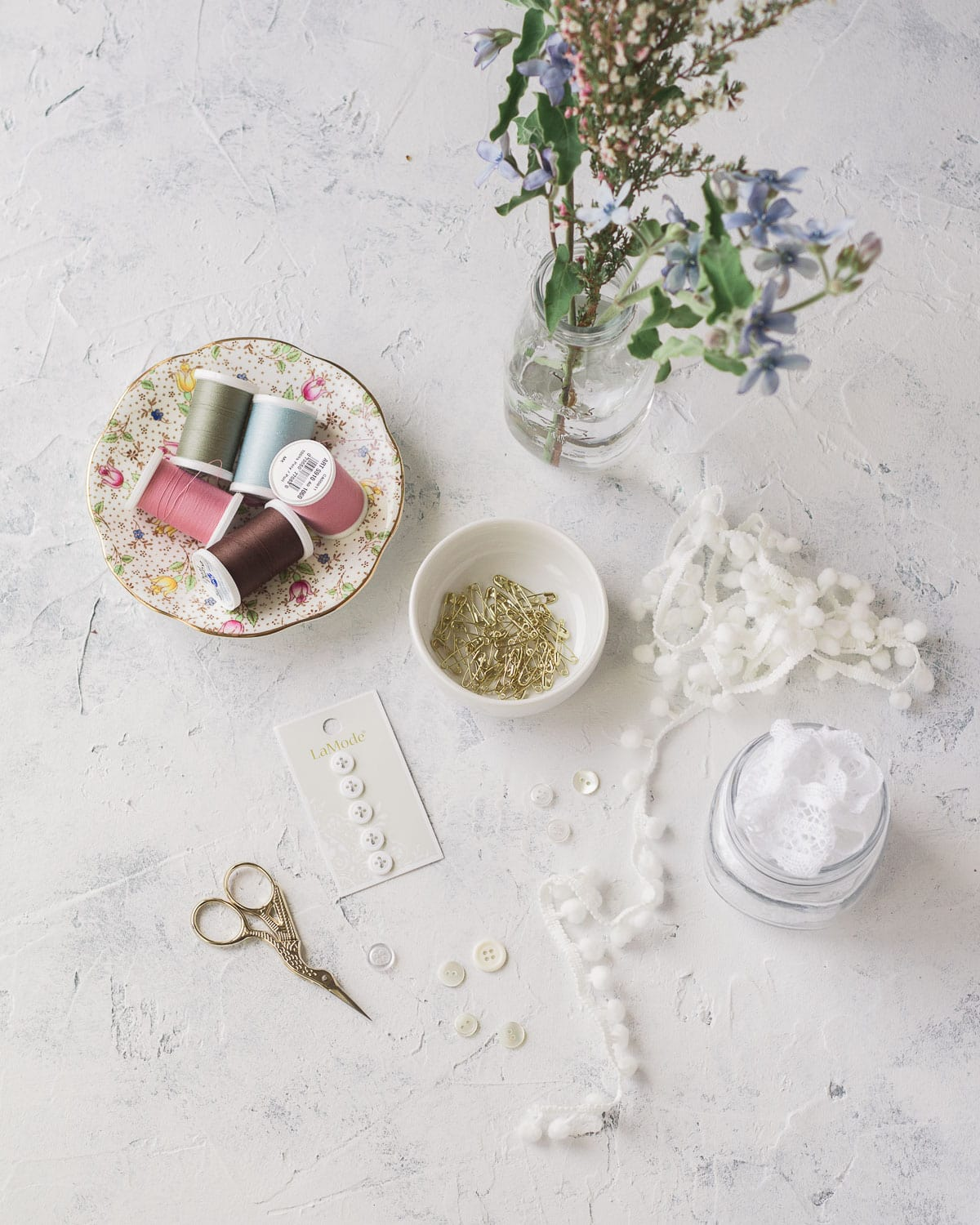 An array of sewing supplies and lace trims on a textured background.