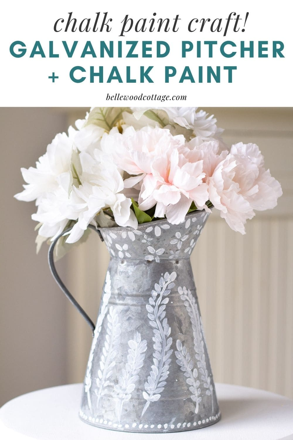 A galvanized pitcher filled with faux florals and decorated with chalk paint.