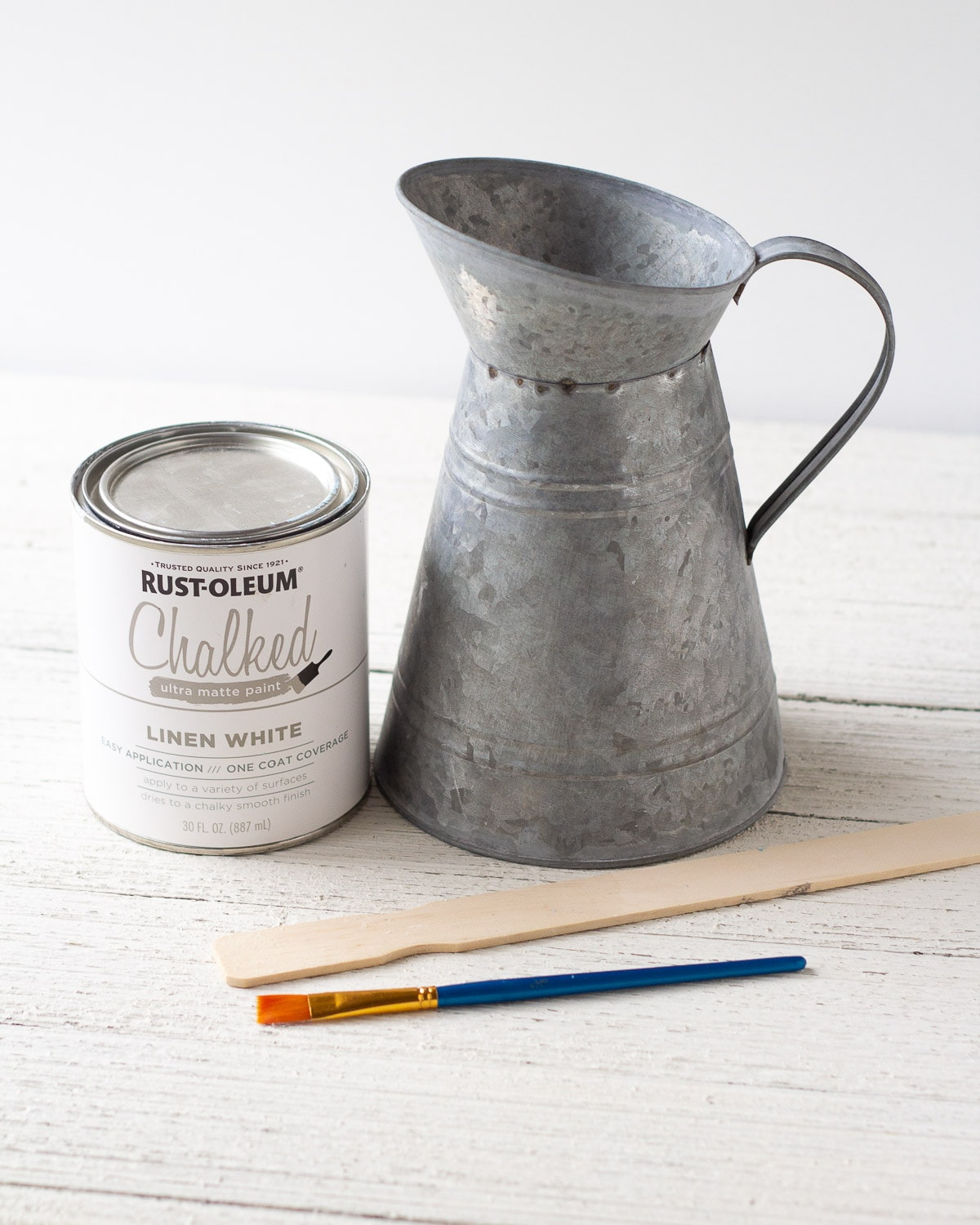 A galvanized pitcher, can of white chalk paint, paint stir stick, and a paintbrush.
