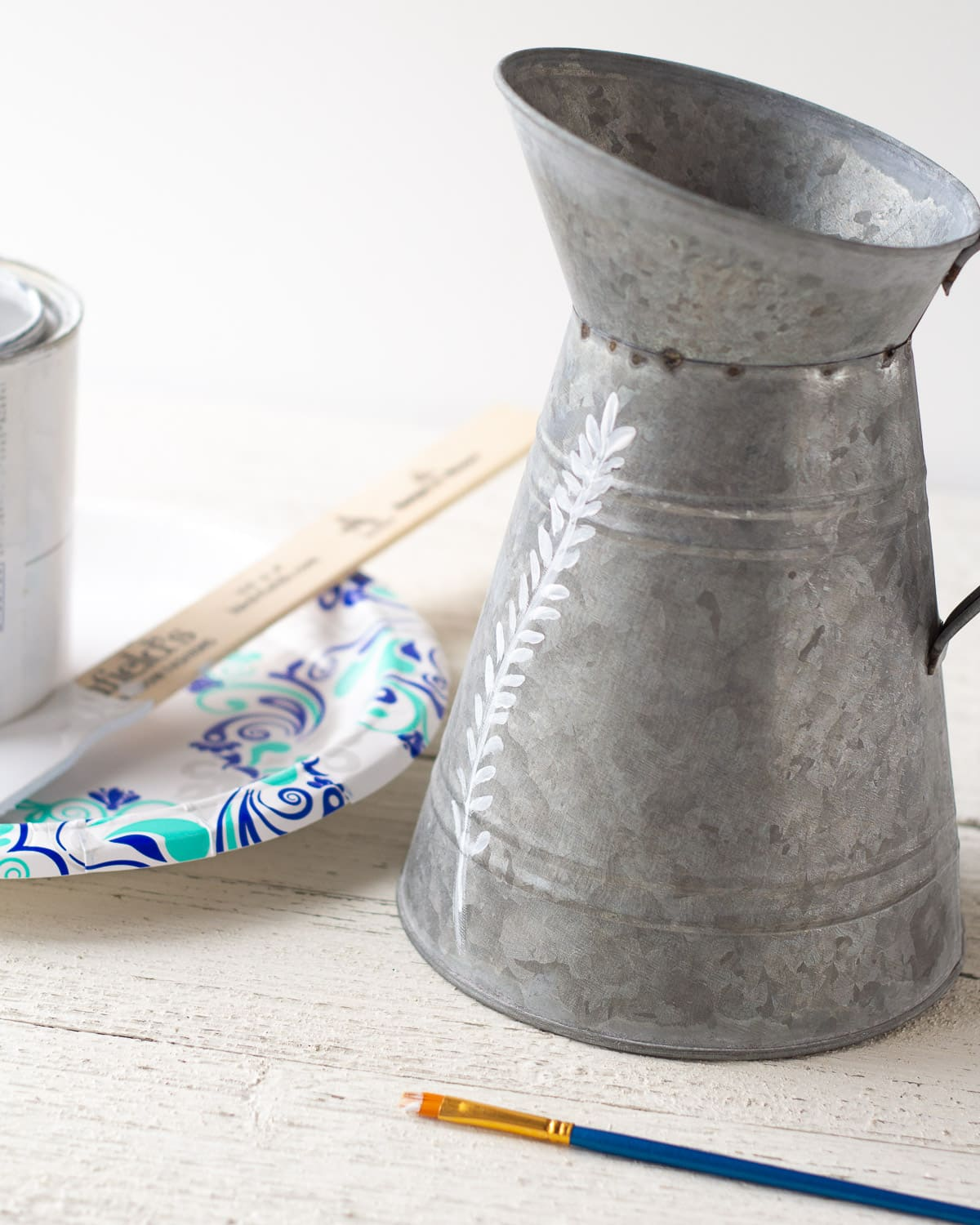 Painting a floral leaf design onto a galvanized pitcher with chalk paint.