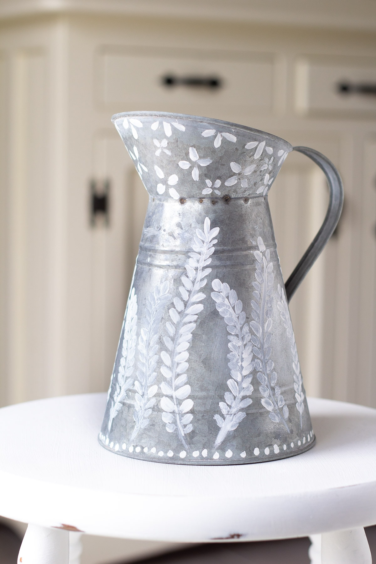 A galvanized pitcher with decorative painting.