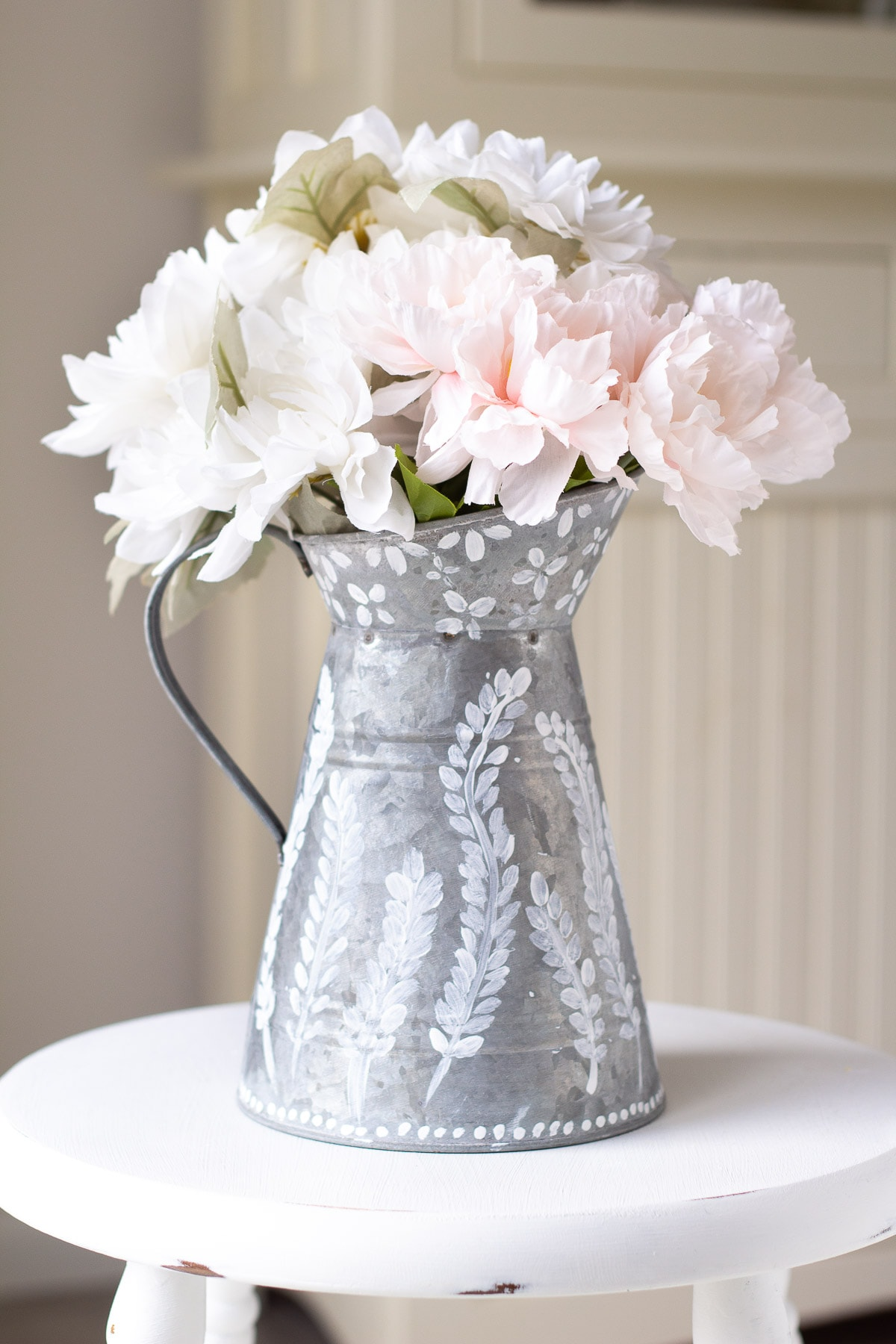 A farmhouse pitcher painted with chalk paint and filled with faux flowers.