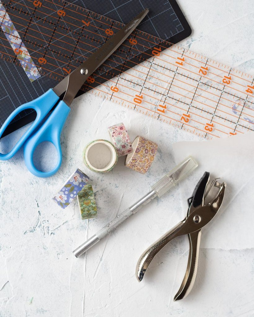 Washi tape, scissors, a craft knife, ruler, and hole punch.