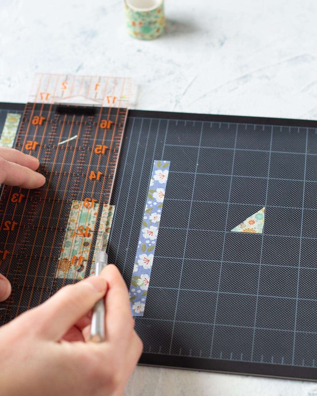 Using a cutting mat, ruler, and a craft knife to cut washi tape into thin strips.