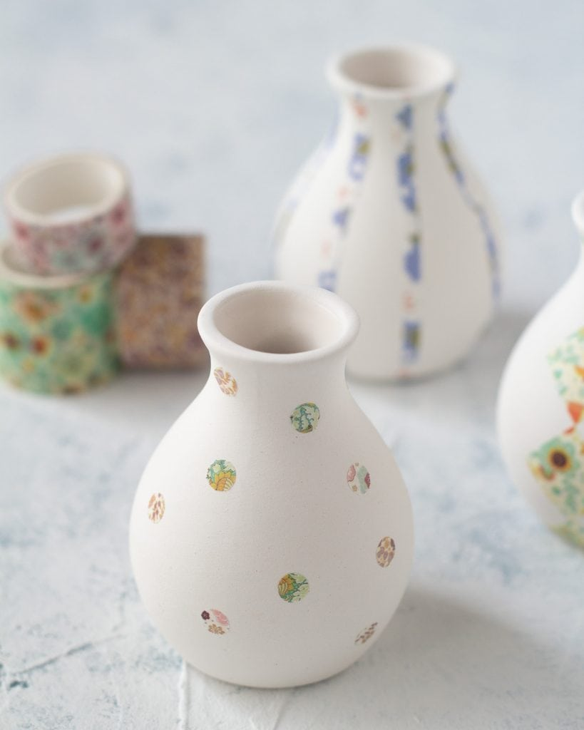 A bud vase decorated with washi tape polka-dots.
