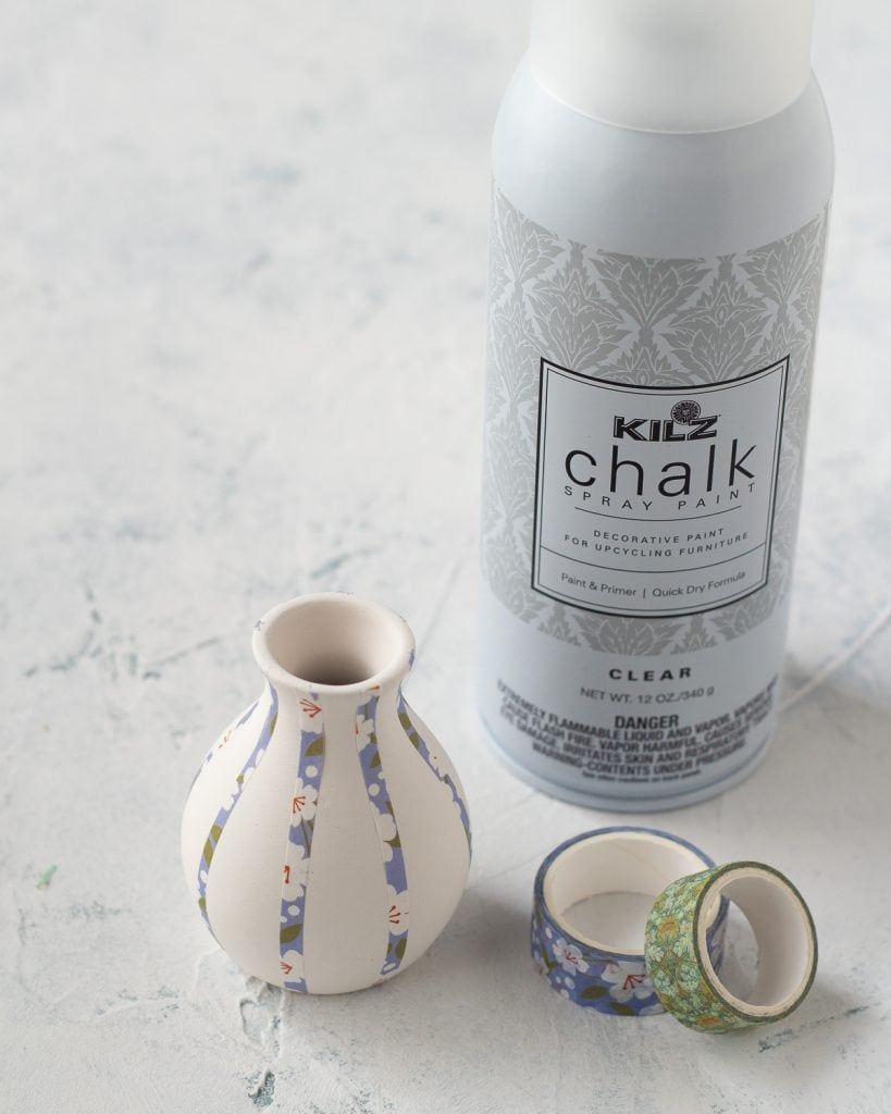 A can of matte clear spray paint and a bud vase decorate with washi tape.