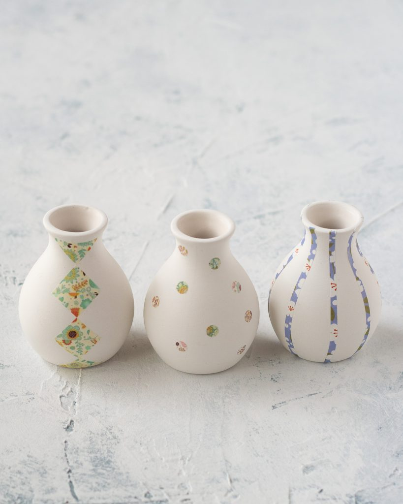 Three small ceramic bud vases decorated with washi tape.