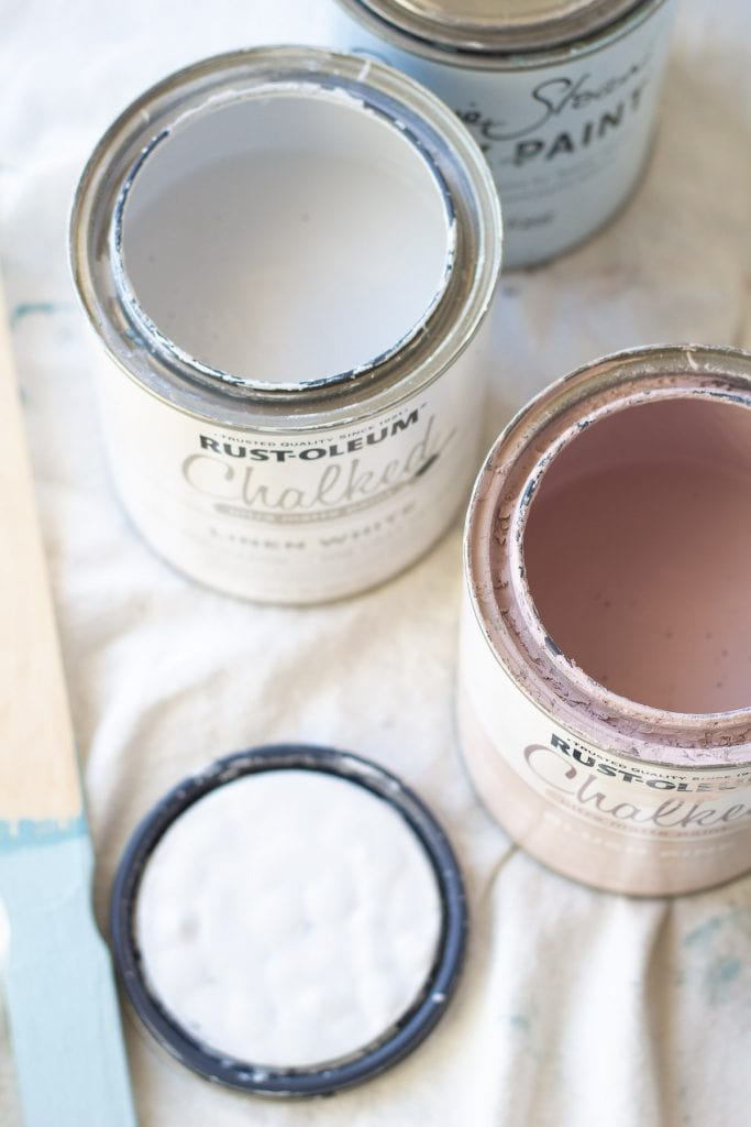 Open cans of white and pink chalk paint on a drop cloth.