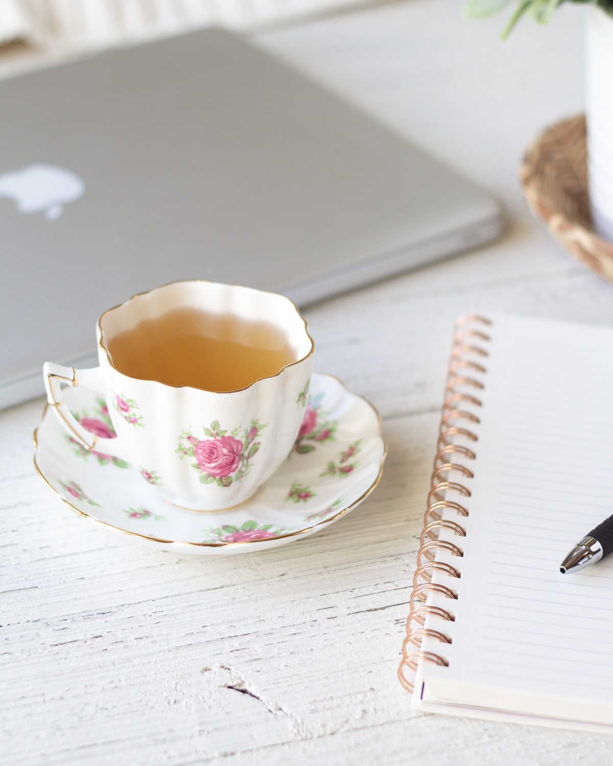 A teacup and notebook on a wooden surface.
