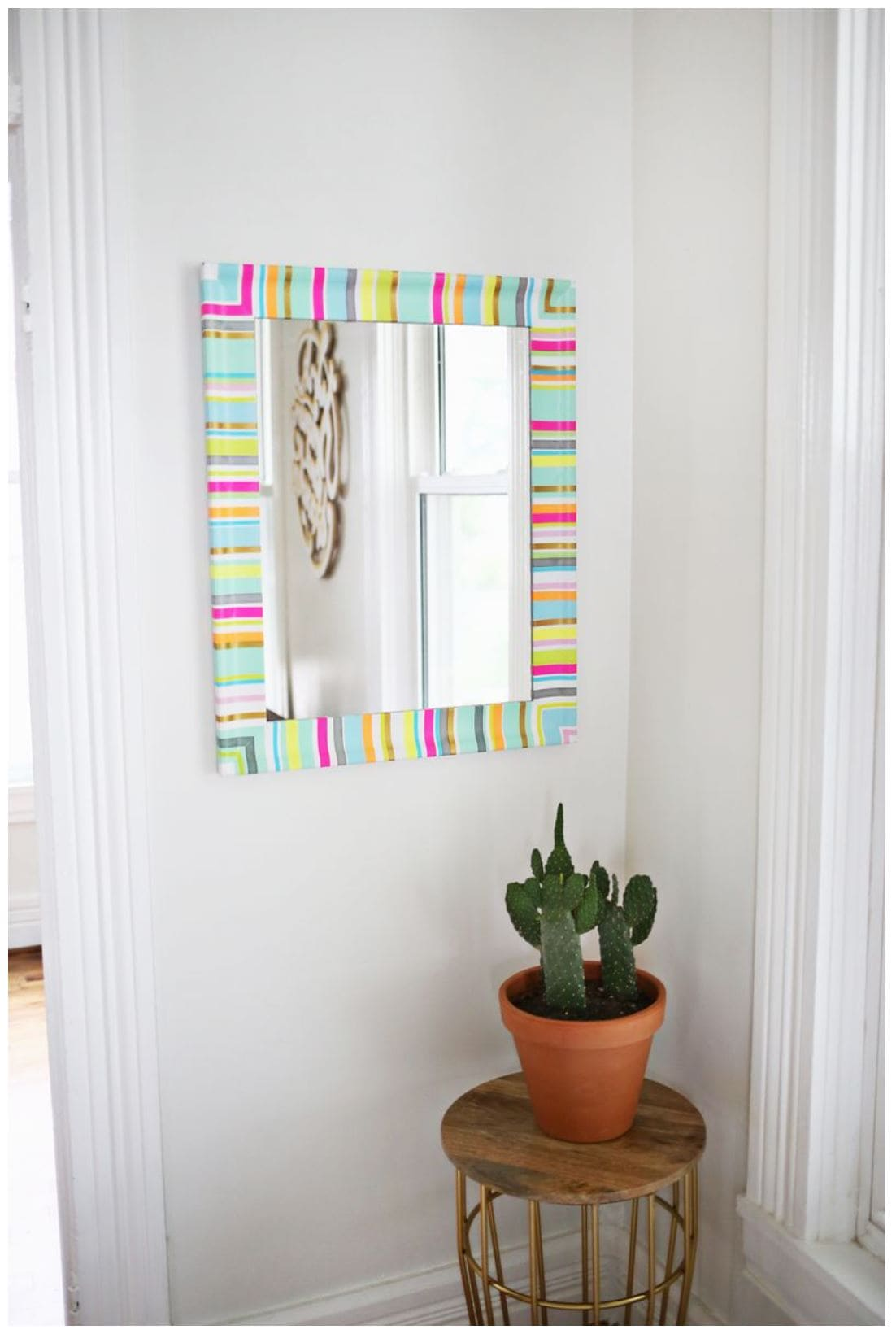 A white mirror decorated with colorful strips of washi tape hanging on a white wall.